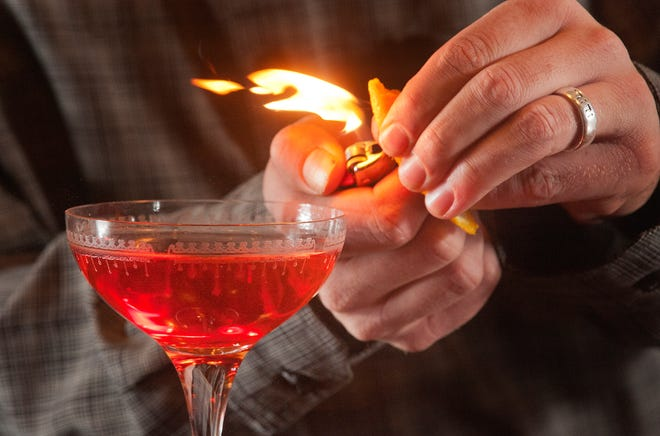 Isaac Fox, owner of La Chasse Restaurant on Bardstown Road puts the final touch on his Smoked Negroni, his bitter sweet version of the classic cocktail. He squeezing an orange peel over the drink, passing the orange oils through a lighter flame igniting them as they fall into the cocktail.November 15, 2018