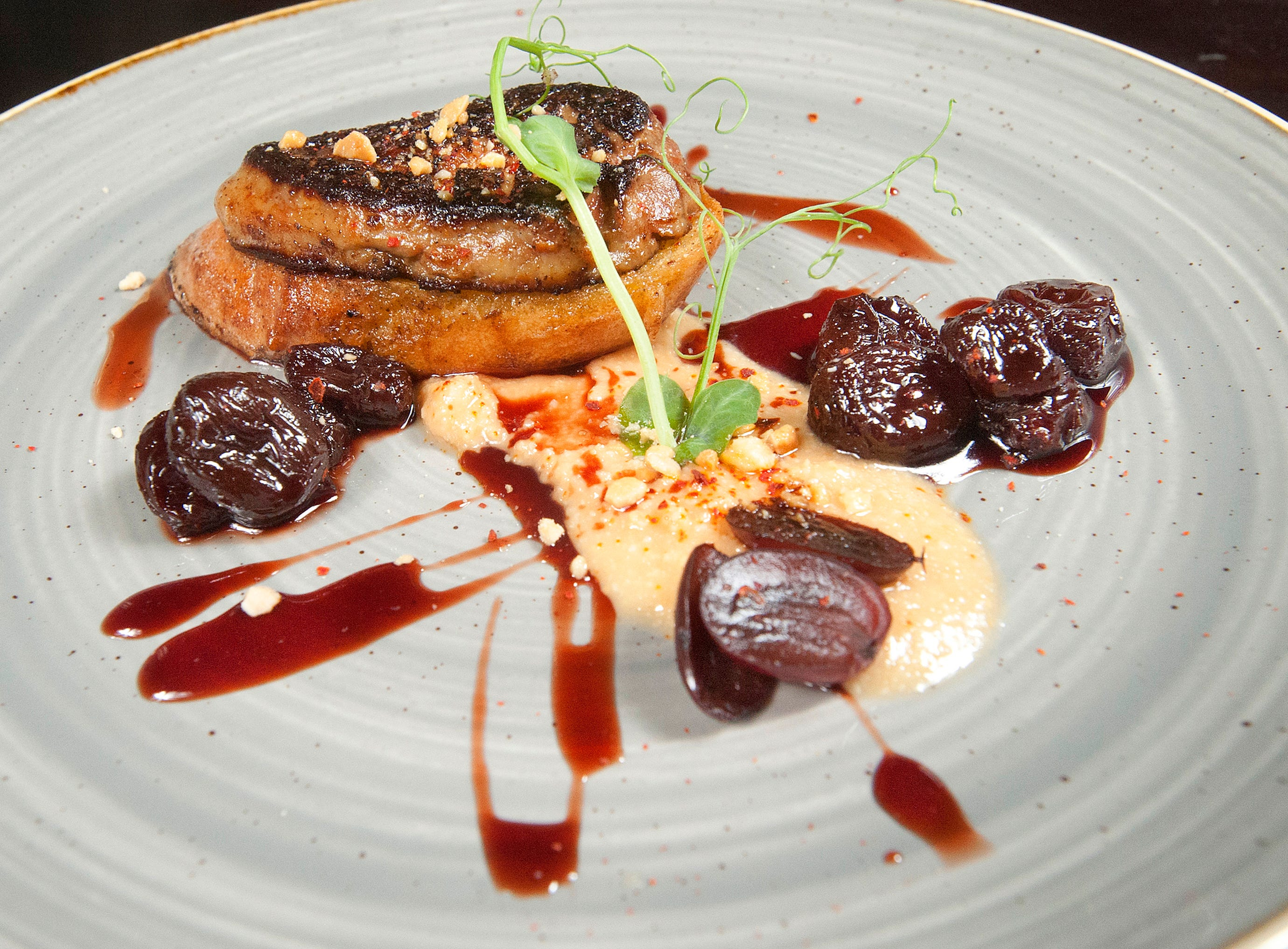 La Chasse Restaurant's Hudson Valley Fois Gras is served over a sliced Blue Dog baguette that has been dipped in black pepper creme anglais. The French toast sits atop a macron almond butter. The dish is accompanied by bred grapes in a port reduction, as well as pickled red grapes.  November 15, 2018