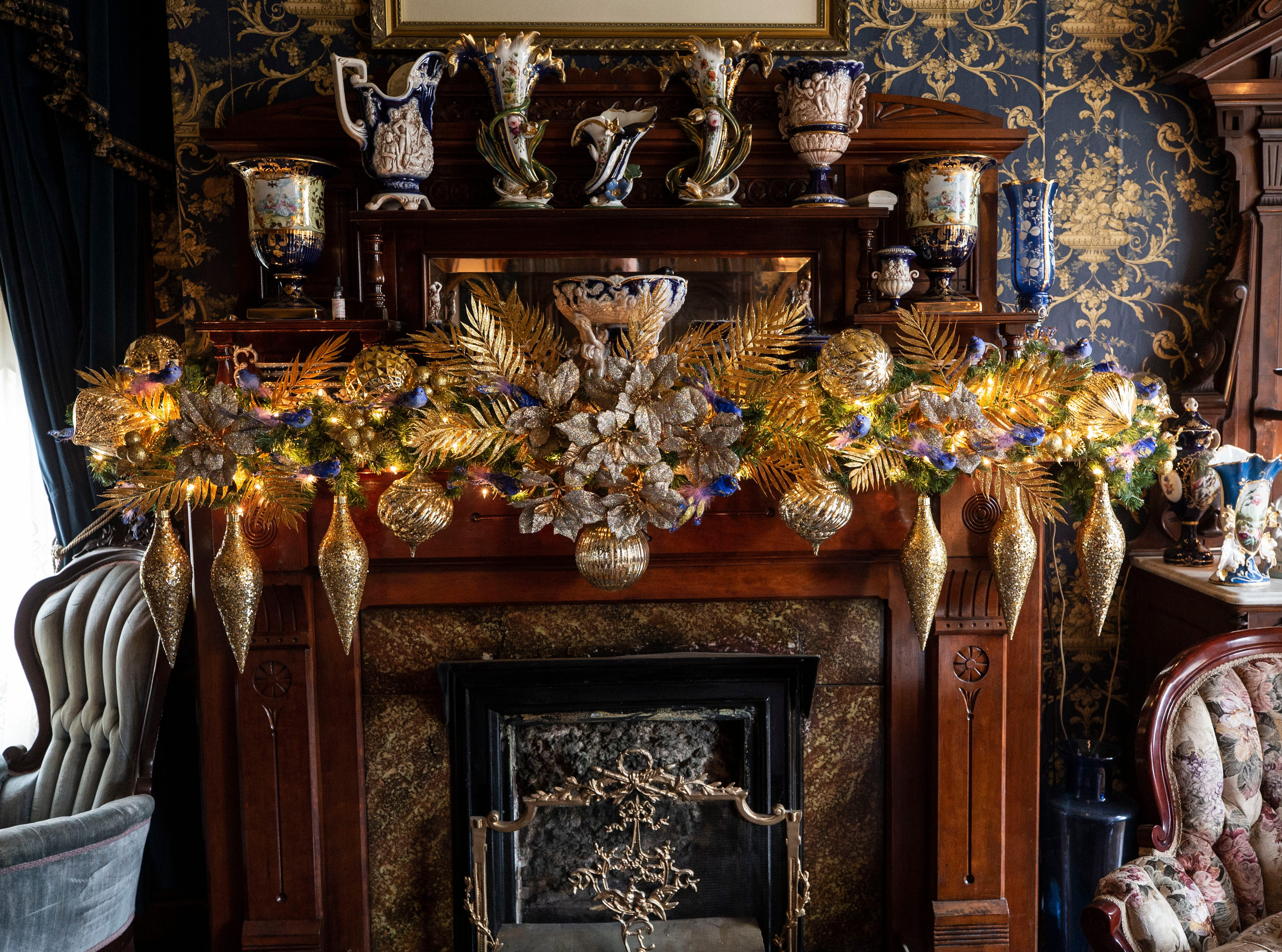 """""""Holidays are my favorite, favorite time. It's fantastic,"""" said homeowner David Brown. A fireplace mantel is decorated with golden ornaments and garland as Victorian-era chairs flank each side."""