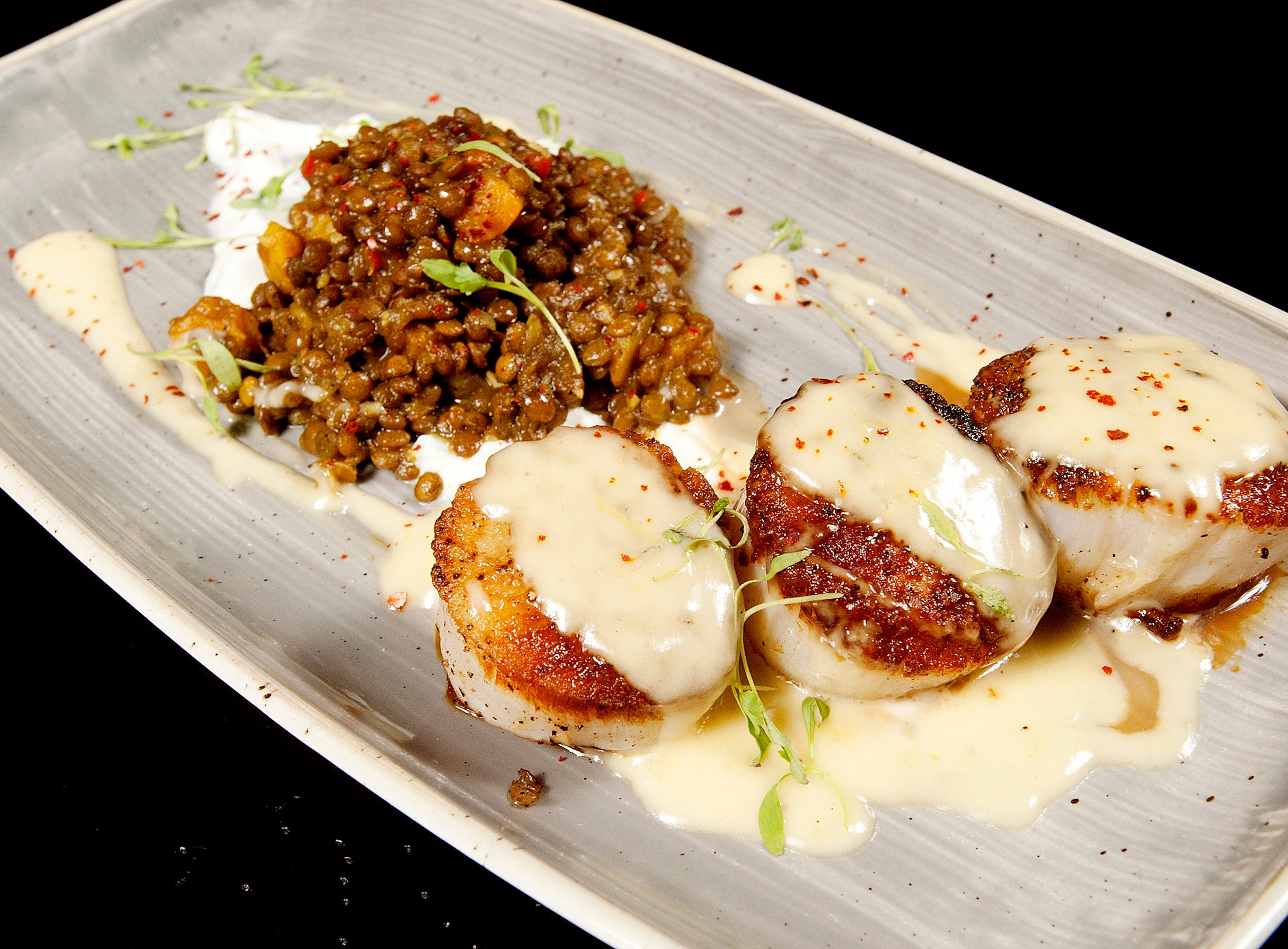 La Chasse Restaurant's seared sea scallops are toped with a lemongrass beurre blanc and are served with curried green French lentils and butternut squash on a cucumber garlic labneh .November 15, 2018