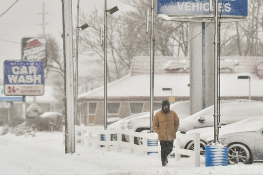 A man walks along Lansing St. in Charlotte Monday morning, Nov. 26, 2018, the morning after the Lansing area's first significant snowfall.