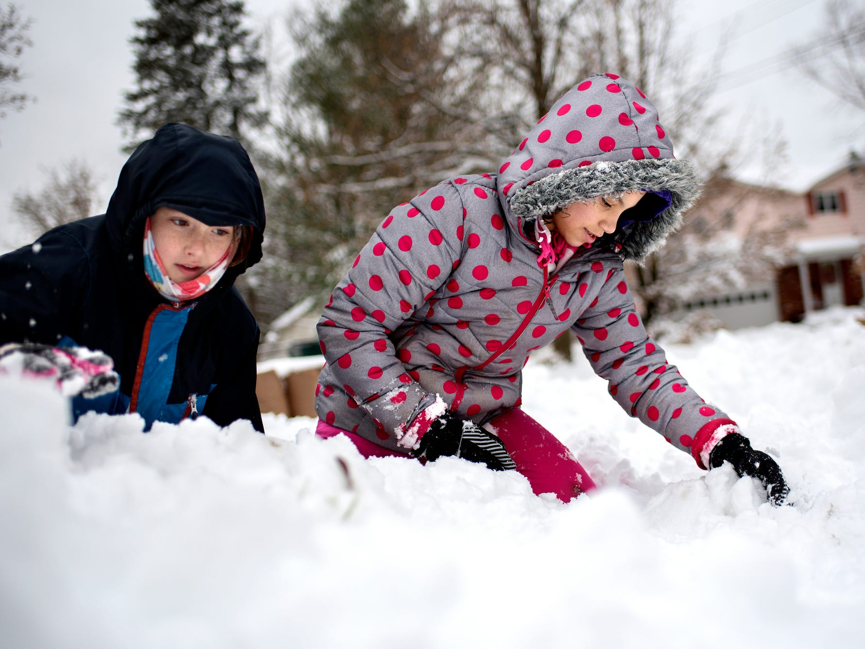 Zadie Denies, 10, left, and neighborhood friend Tyanna Morgan, 11, build a fort in Denies' yard on Monday, Nov. 26, 2018, in Lansing. School was cancelled for the two girls.