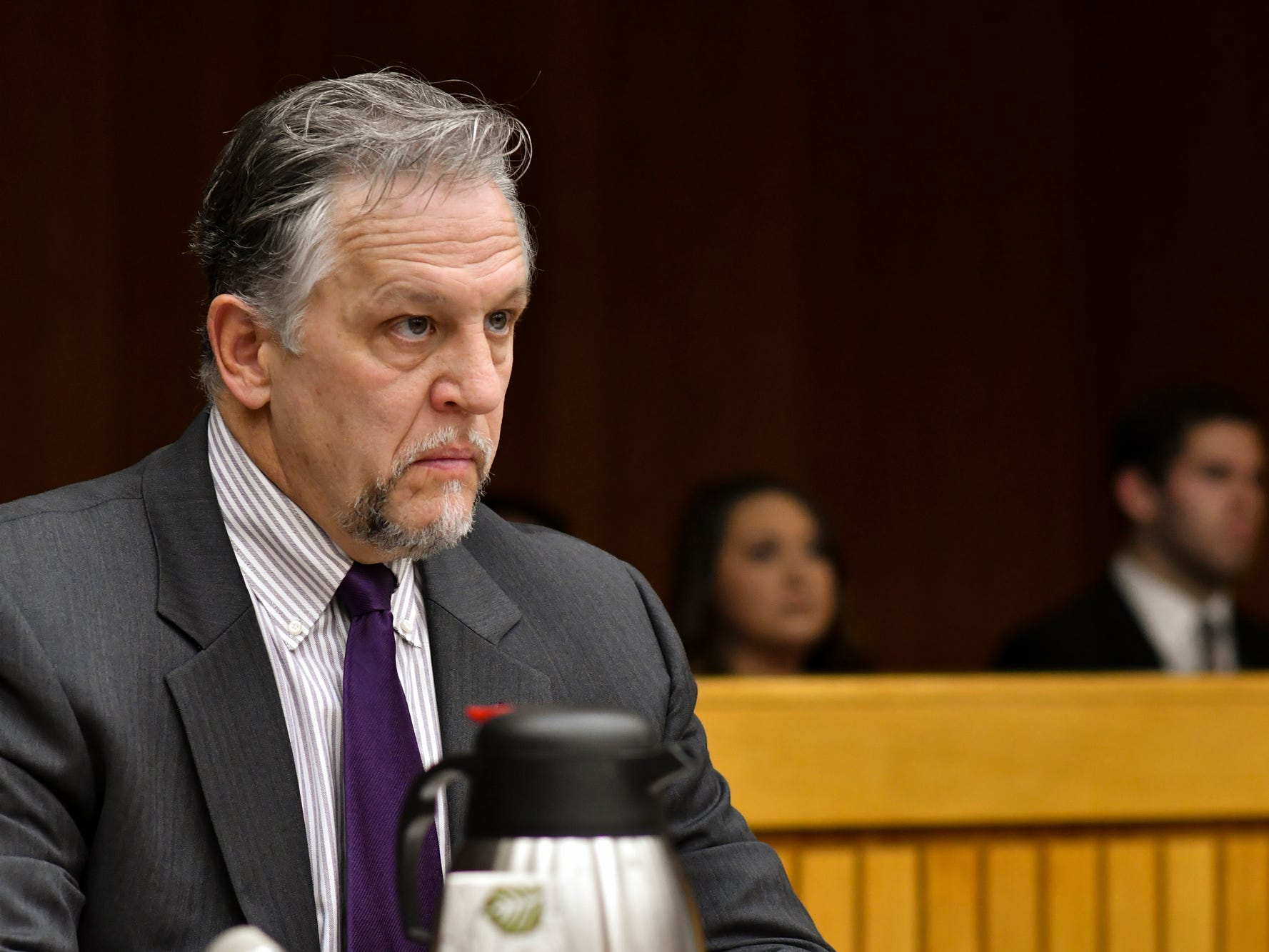 Assistant Attorney General Scott Teter listens as Judge Julie Reincke reads charges against former MSU President Lou Anna Simon, Monday, Nov. 26, 2018, during Simon's arraignment in Eaton County.  Simon faces four charges of lying to police related to the Larry Nassar investigation.  [AP Photo/Matthew Dae Smith/Lansing State Journal]