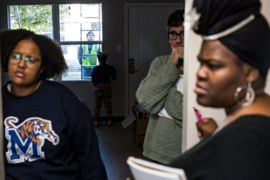 A worker is seen outside while Shannon Washington, far right, talks with Britney Thornton, left, and Roy Barnes at Pendleton Place Apartments in Orange Mound. Renovation efforts are underway at the aging housing complex, but some tenants say their complaints aren't being addressed.