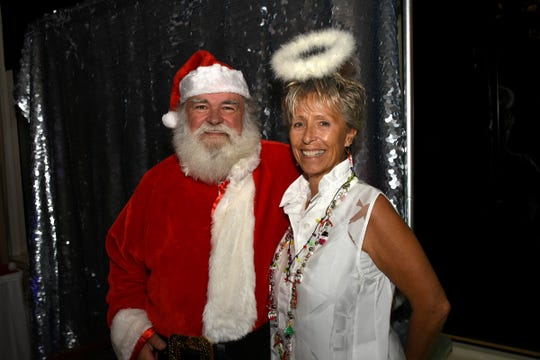 Sandi Sims-Ravage, who was recognized for her work with the chamber's social committee, is decked out in white, complete with halo, accompanied by Santa.