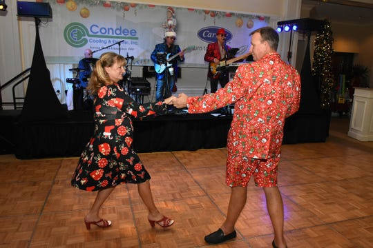 Curt Koon, in a festive Christmas suit, dances with wife Jacquie, in her own holiday dress, at Saturday's Chamber-sponsored bash.