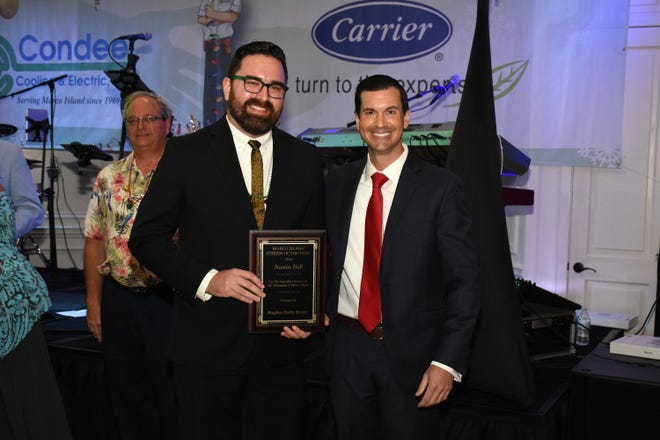 Marco Eagle Manager T.J. Boone presents Austin Bell, left, curator of collections for the Marco Island Historical Society, with the Naples Daily News Citizen of the Year award on Saturday at Hideaway Beach Club.