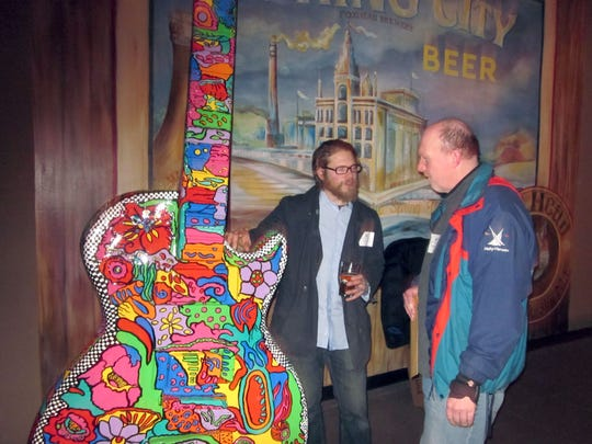 Ramona Audley painted a 10-foot guitar for the Waukesha GuitarTown project in 2013. Standing next to her large artwork is Steve Coughlin of Waukesha (left) and Albin Erhart of Hartland.