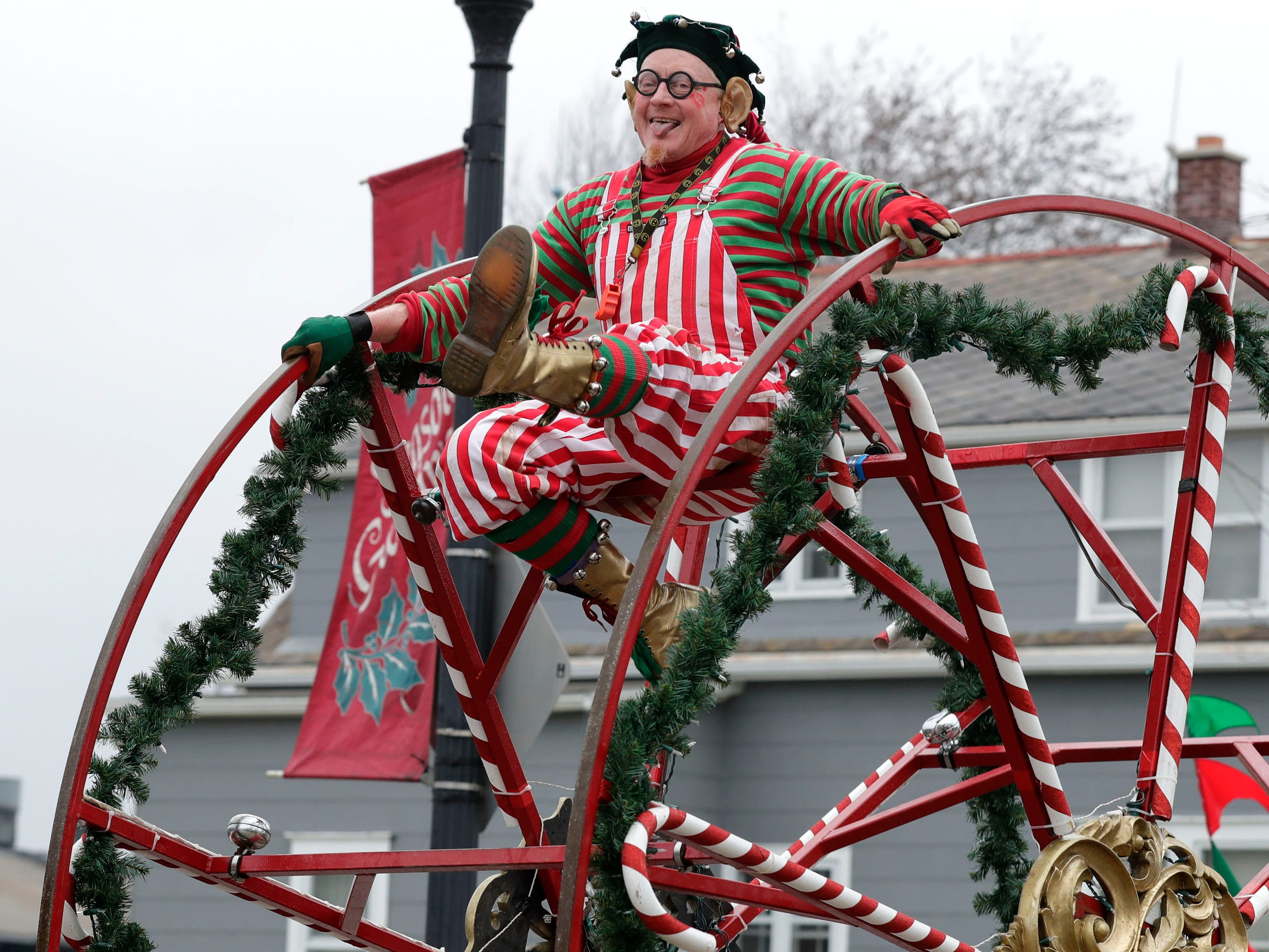 "Rob Summerbell, ""The Wacky Wheeler,"" performs in the Grafton Christmas Parade, one of his three final holiday parades.  Summerbell is finally ""parking the wheel"" after performing in more than 1,200 parades over 18 years. He loves the crowds, but because of sore knees he is finishing the year with three holiday parades."
