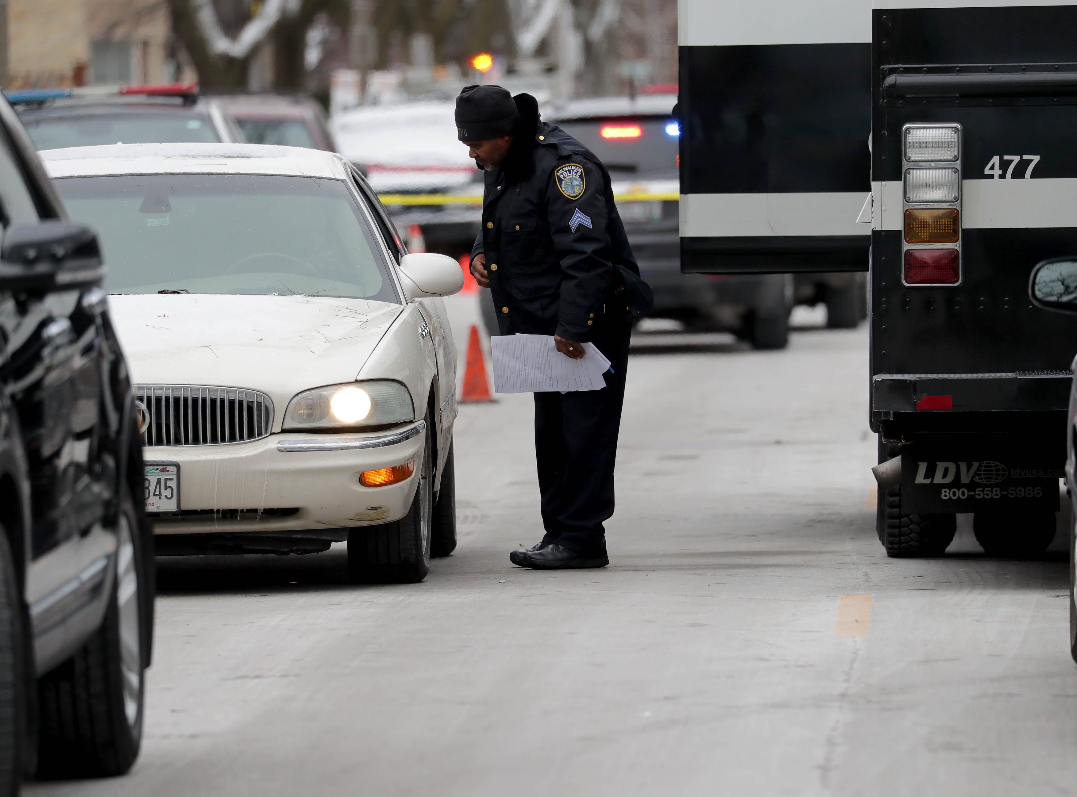 A Milwaukee police officer talks to a motorist while investigating the scene of what is believed to be an officer-involved shooting.