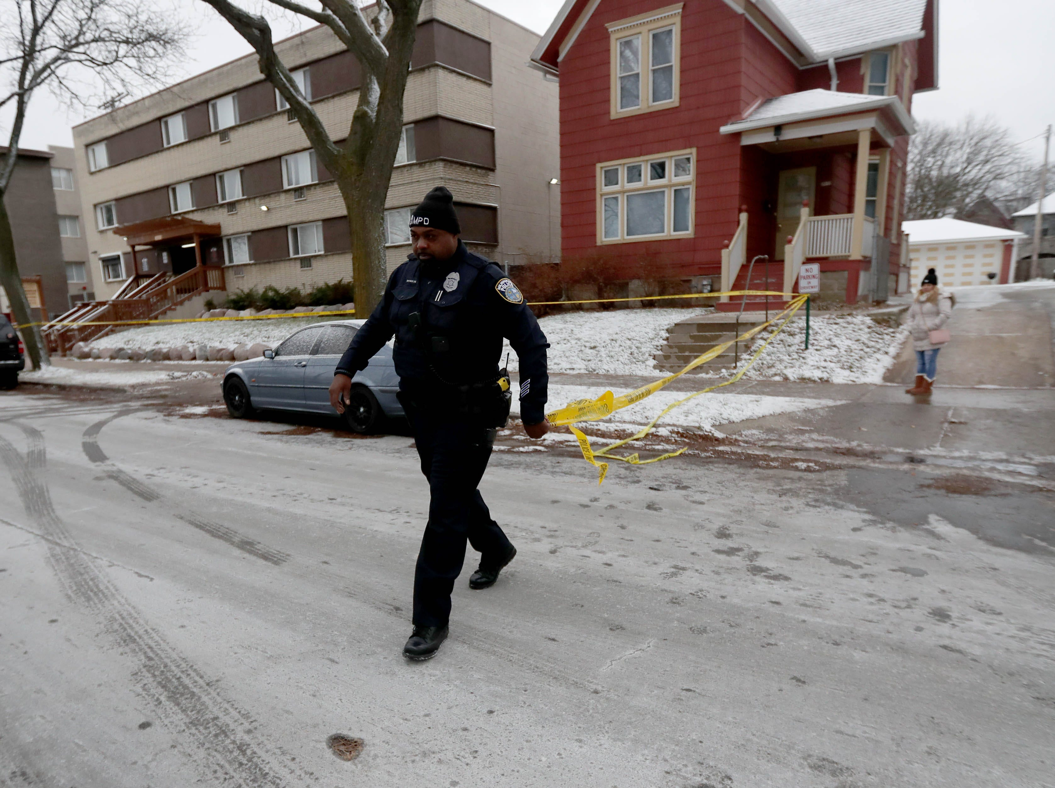 A Milwaukee police officer puts up police tape while officers investigate.