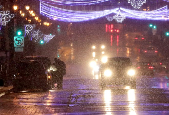 Snow falls on West Wisconsin Avenue in downtown Milwaukee in November as a mix of sleet and snow hit the area.