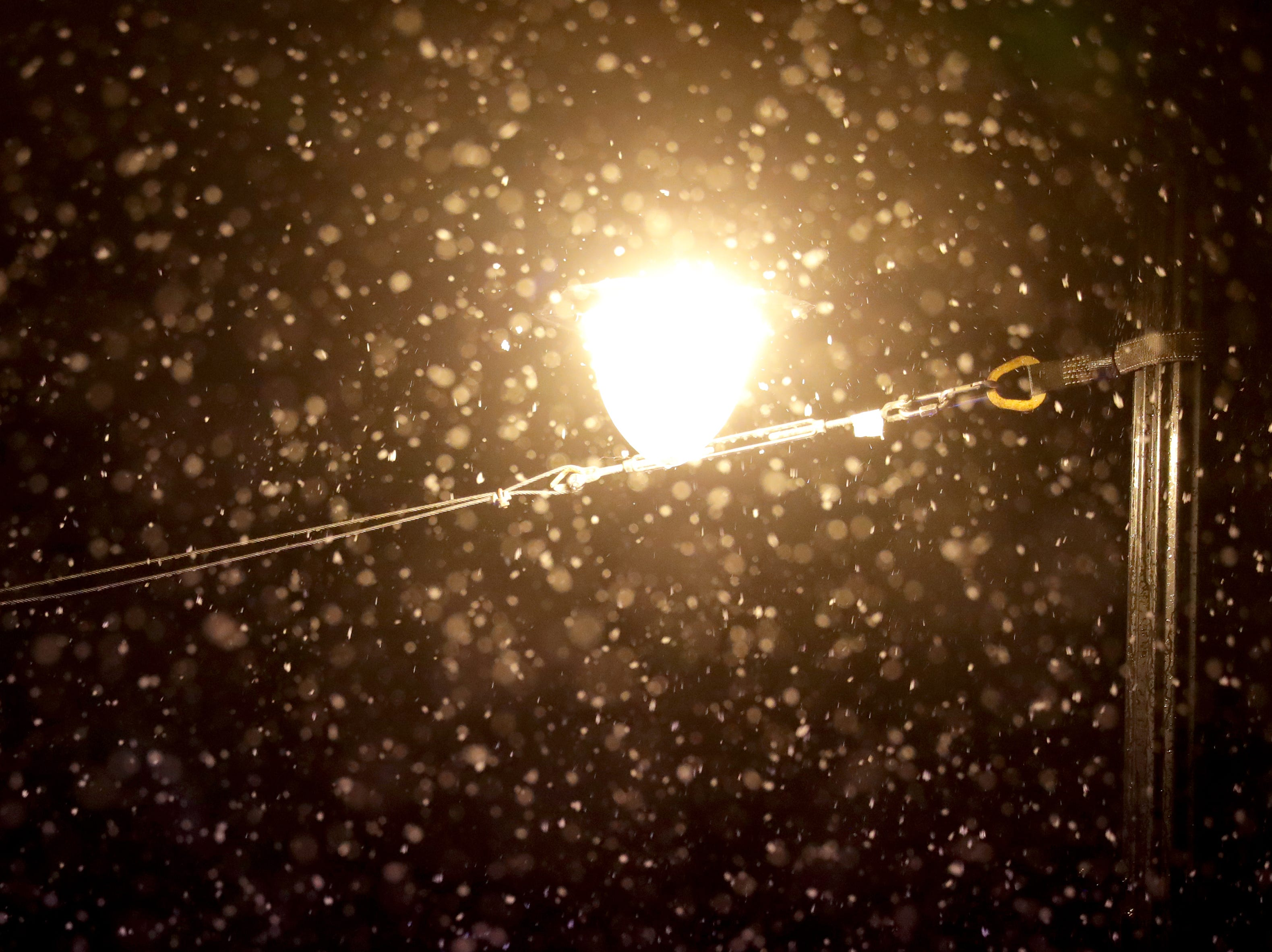 Snow falls over a streetlight near West Wisconsin Avenue in Milwaukee as a mix of sleet and snow fell Sunday night in downtown Milwaukee.