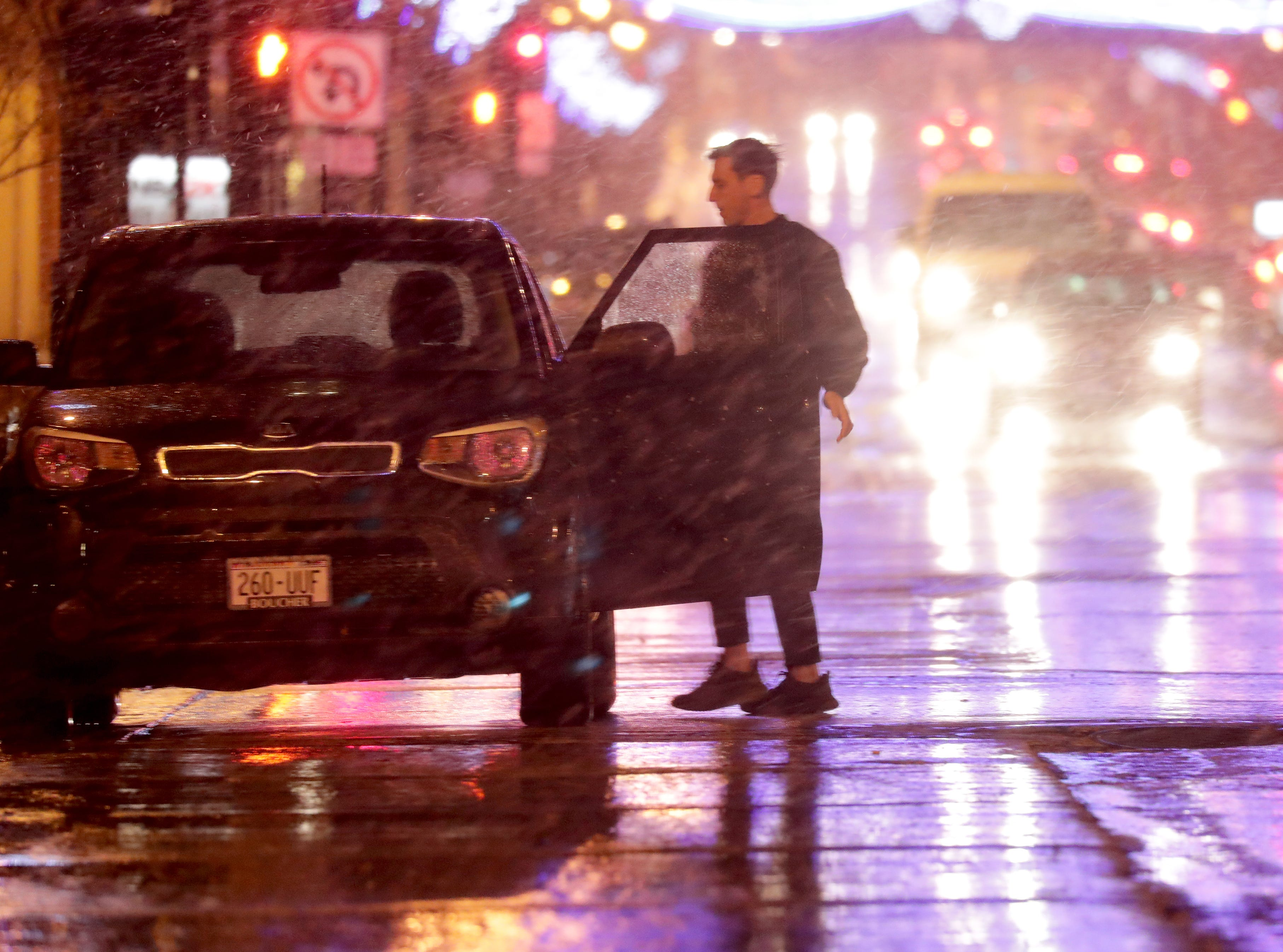 A motorist gets into his car on West Wisconsin Avenue in Milwaukee as a mix of sleet and snow fell Sunday night in downtown Milwaukee.
