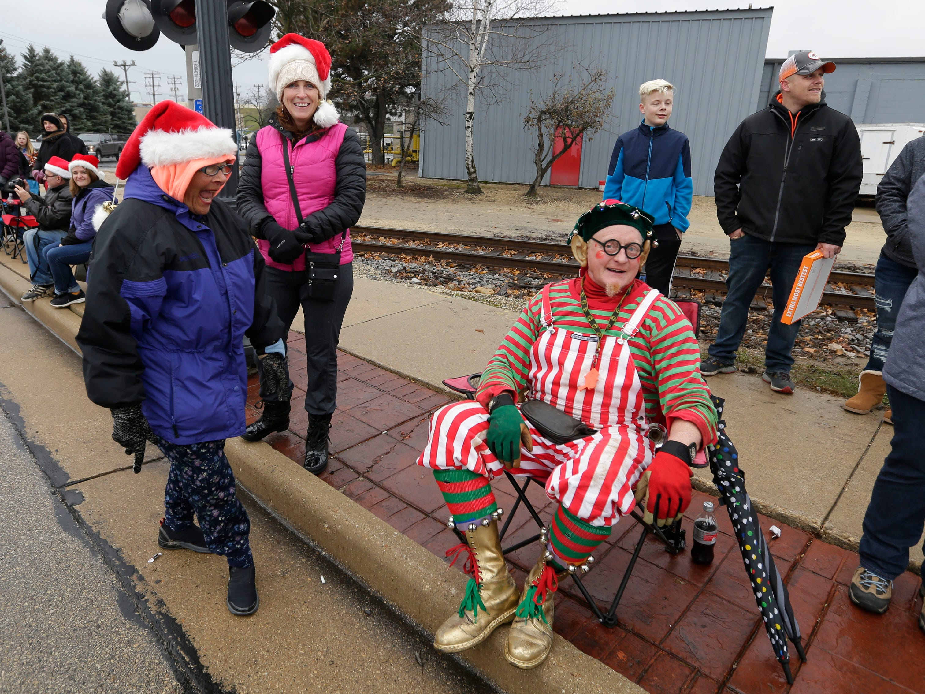 While his wheel slowly rolls past him, Rob Summerbell  teases the crowd by sitting down before continuing his performance in the Grafton Christmas Parade.