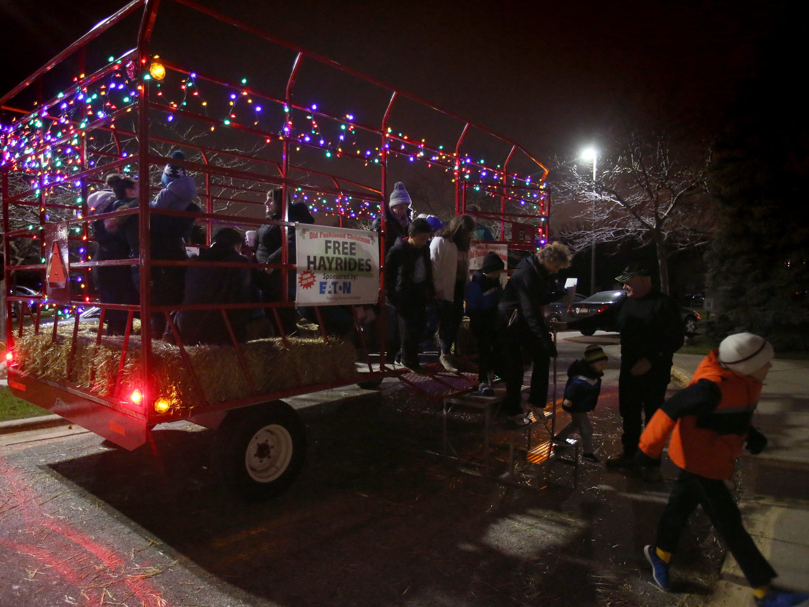 Guests to the Old Fashioned Christmas festivities at City Hall unload from a hayride about the area on Nov. 24.
