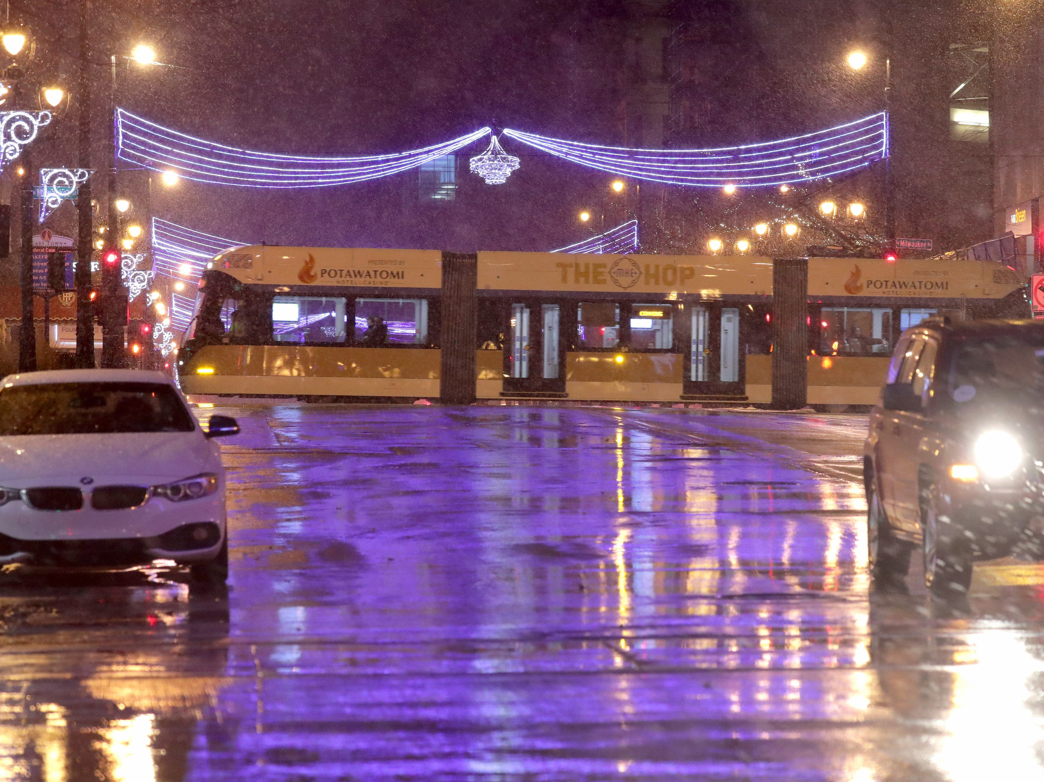 The Milwaukee streetcar, The Hop, passes across East Wisconsin Avenue at North Milwaukee Street in Milwaukee as a mix of sleet and snow fell Sunday night in downtown Milwaukee.