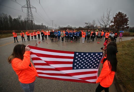 Runners and walkers pause for the Star Spangled Banner before the start of the Kelly Johnson Foundation's first Turkey Trot 5K Run/Walk at Mitchell Park in Brookfield on Nov. 24, 2018.