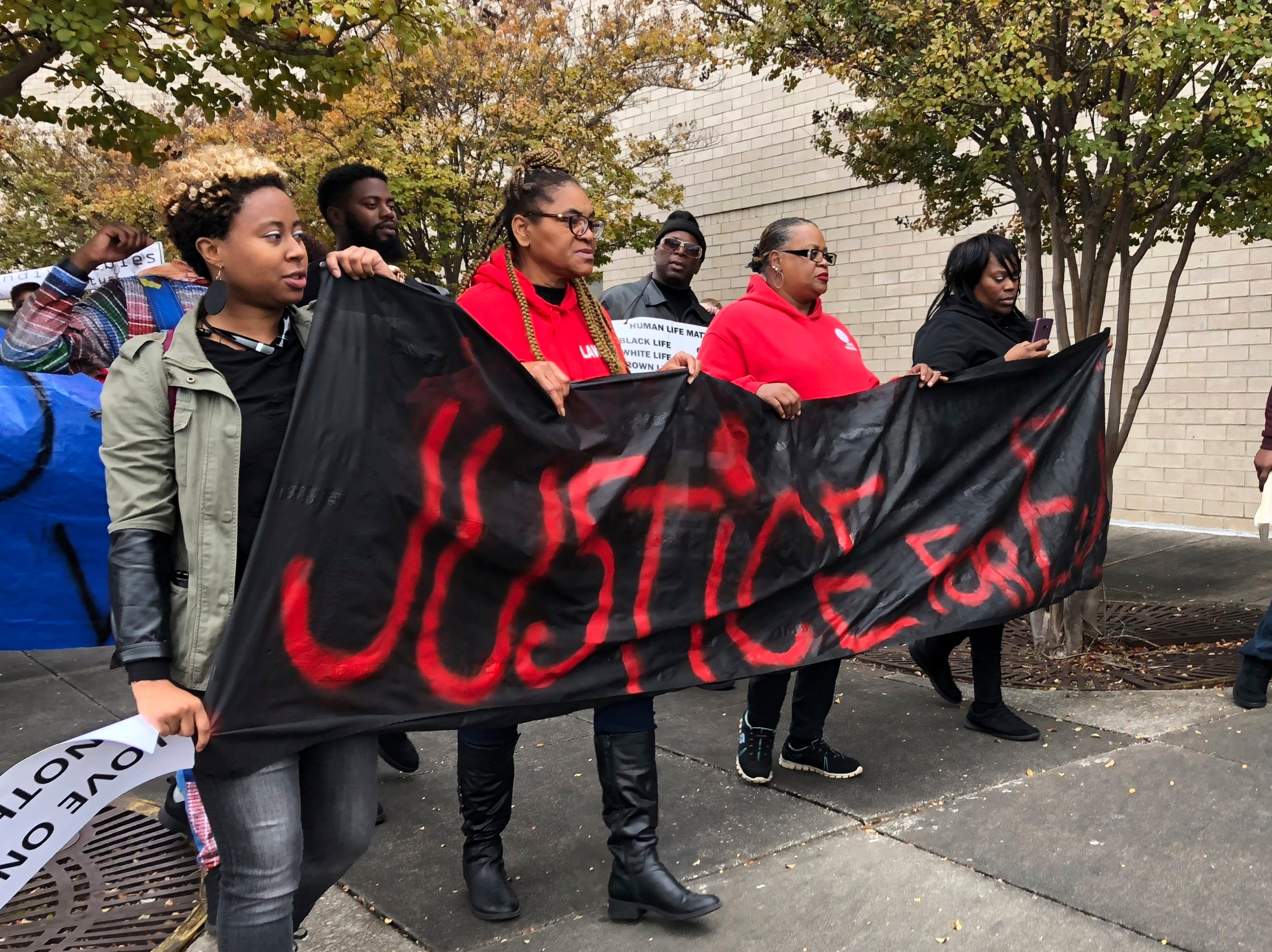 """Protestors carry a sign reading """"Justice for E.J."""" during a protest at the Riverchase Galleria in Hoover, Ala., Saturday, Nov. 24, 2018. A police shot and killed 21-year-old Emantic Fitzgerald Bradford, Jr. of Hueytown while responding to a shooting at the mall on Thanksgiving evening. Police said Bradford was fleeing the scene with a weapon. Hoover police initially told reporters Bradford had shot a teen at the mall, but later retracted the statement. (AP Photo/Kim Chandler)"""