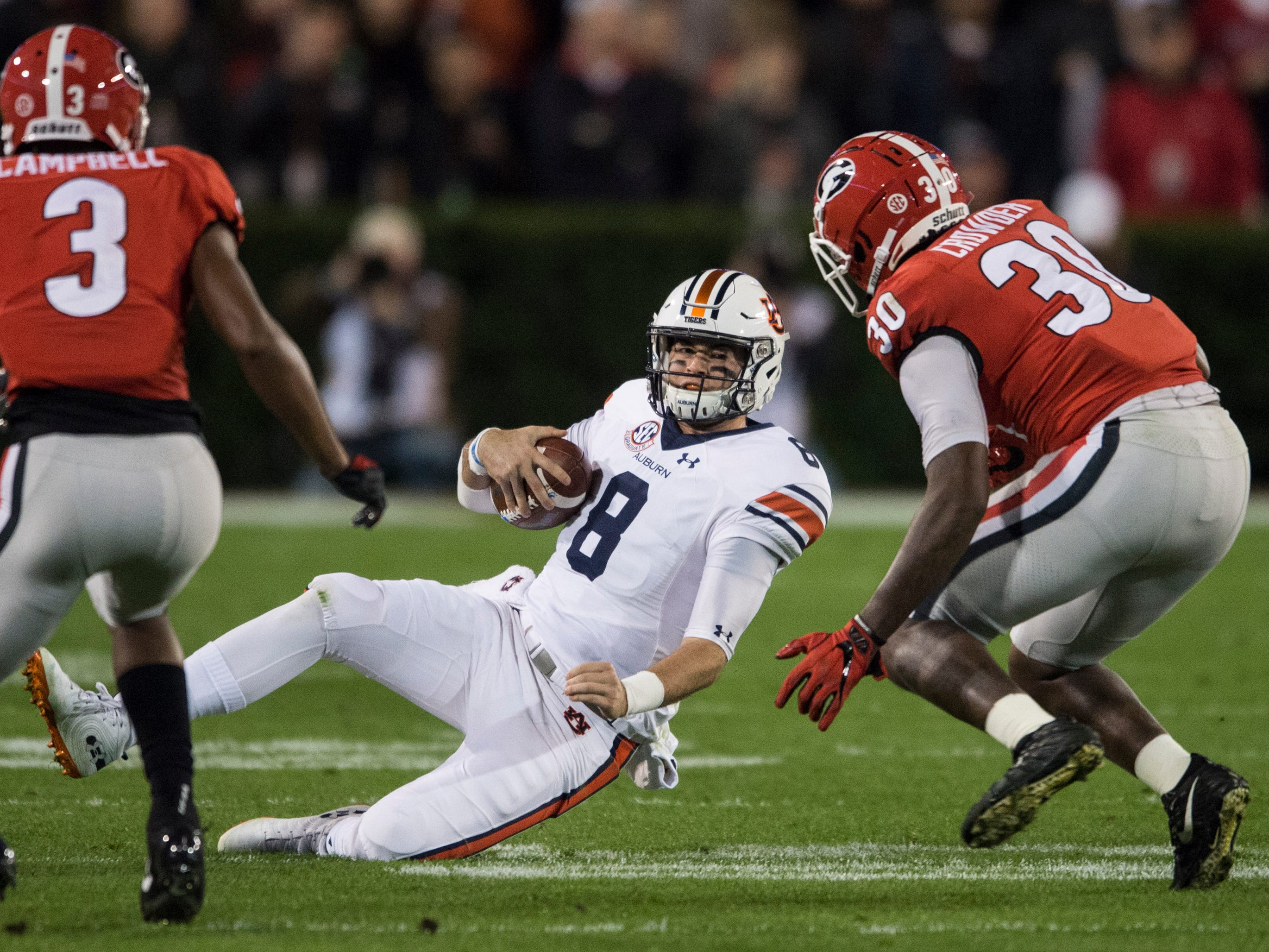 Auburn quarterback Jarrett Stidham (8) slides after a short run against Georgia  at Sanford Stadium in Athens, Ga., on Saturday, Nov. 10, 2018. Georgia leads Auburn 20-10 at halftime.