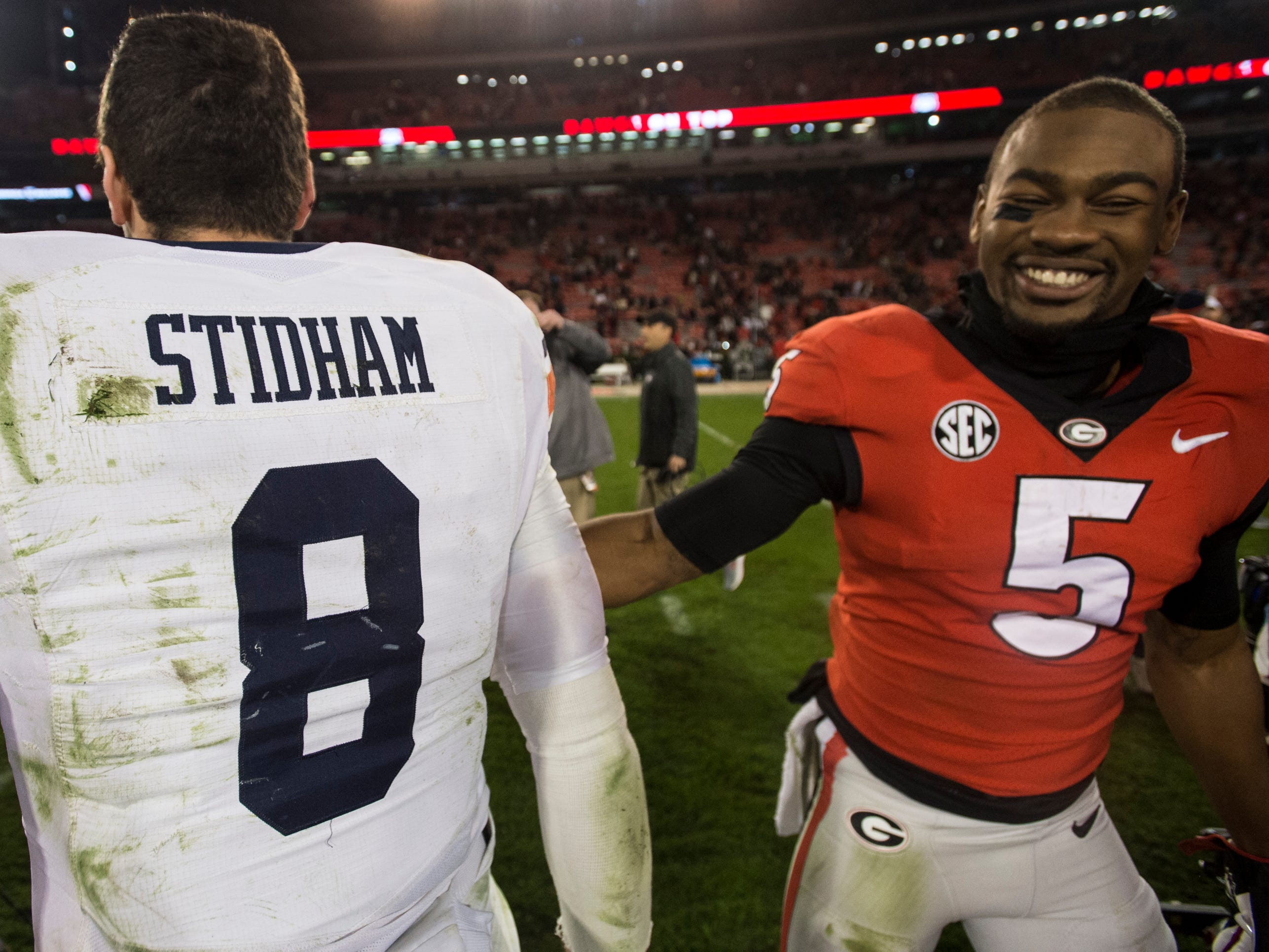 Auburn quarterback Jarrett Stidham (8) and Georgia wide receiver Terry Godwin (5) shake hands after the game at Sanford Stadium in Athens, Ga., on Saturday, Nov. 10, 2018. Georgia defeated Auburn 27-10.