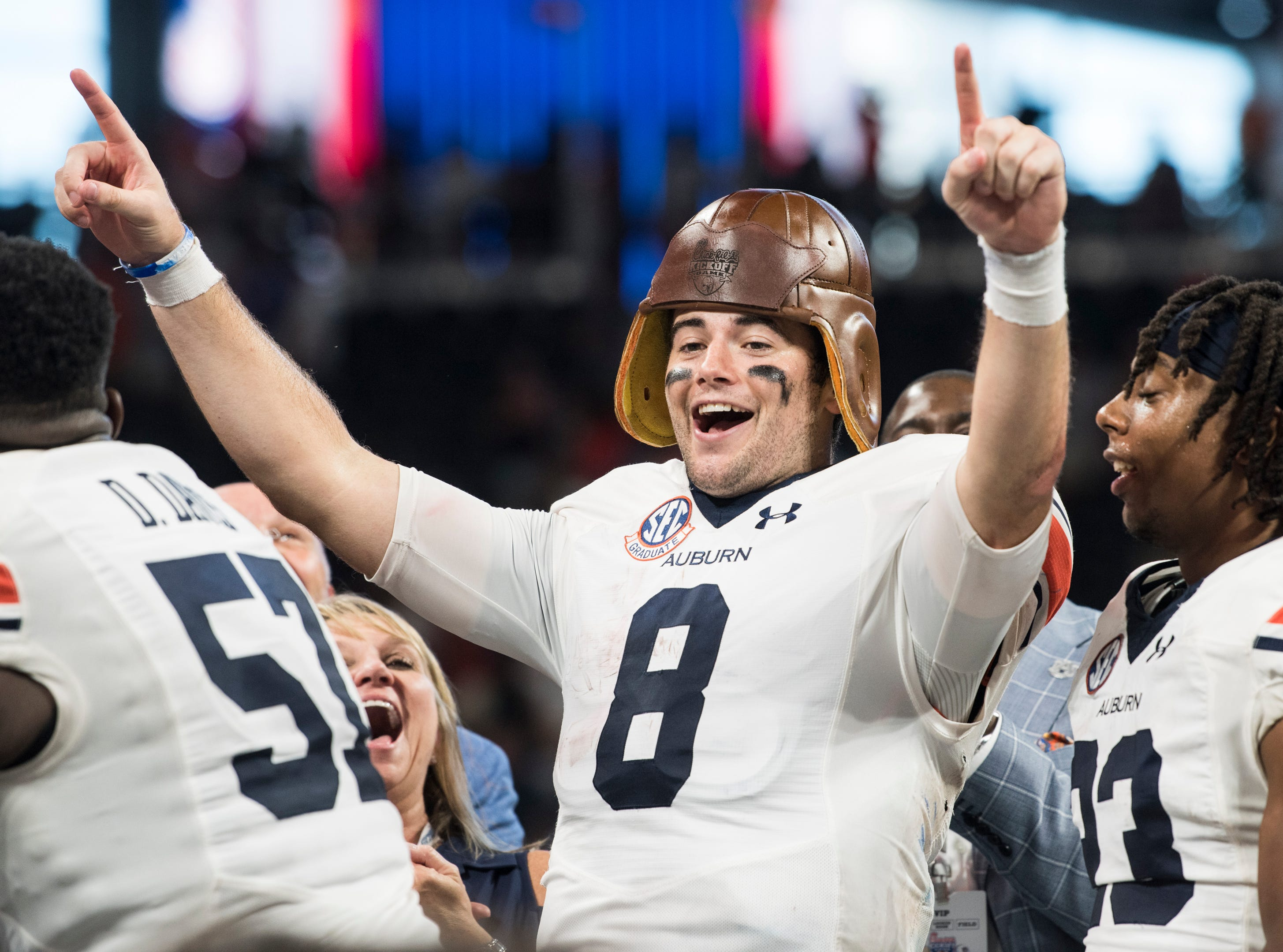 Auburn's Jarrett Stidham (8) wears the old leather helmet trophy at Mercedes-Benz Stadium in Atlanta, Ga., on Saturday, Sept. 1, 2018. Auburn defeated Washington 21-16 in the Chick-fil-a Kickoff Game.