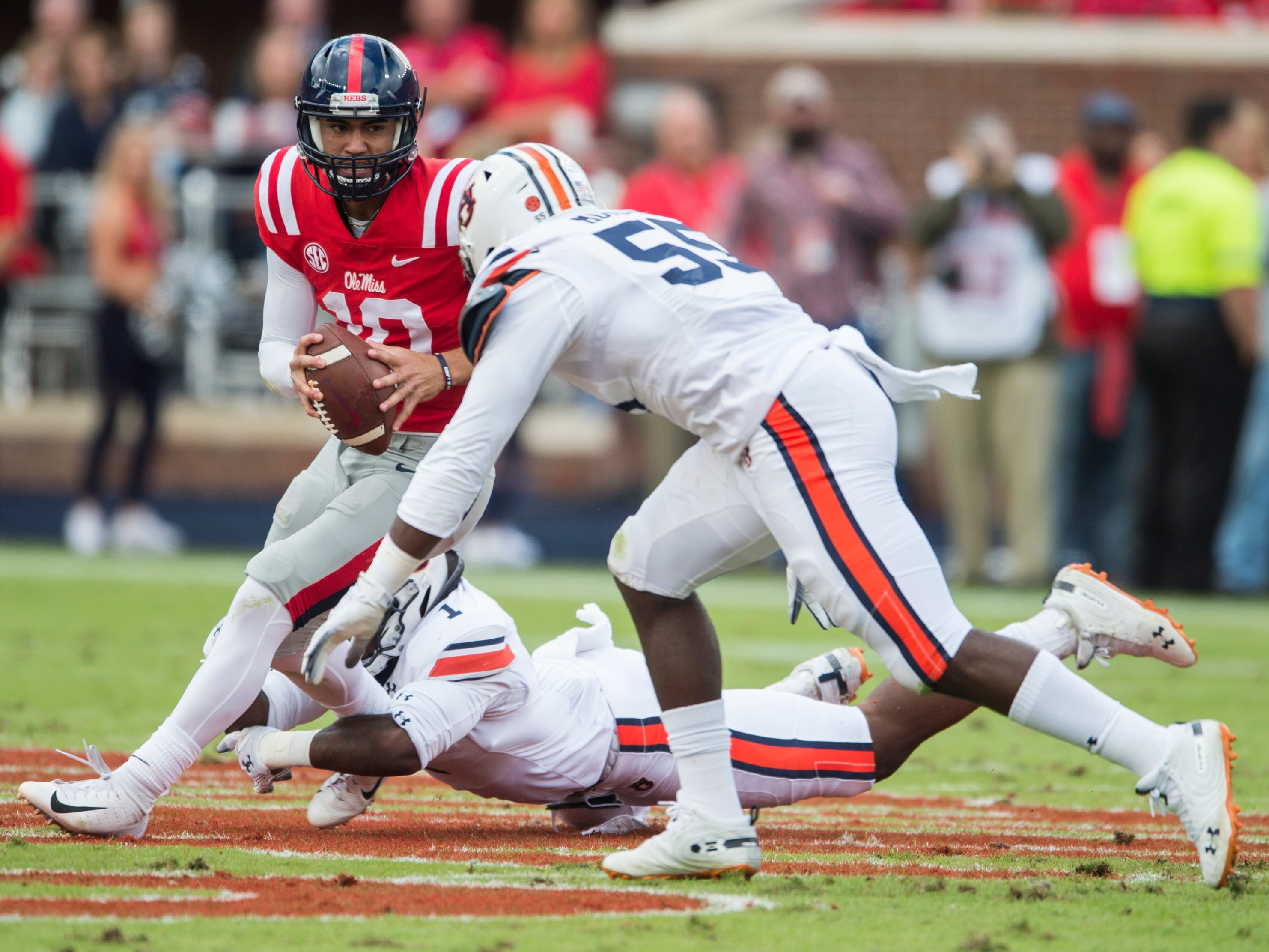 Ole Miss' Jordan Ta'amu (10) avoids Auburn defenders at Vaught-Hemingway Stadium in Oxford, Miss., on Saturday, Oct. 20, 2018. Auburn leads Ole Miss 10-6 at halftime.