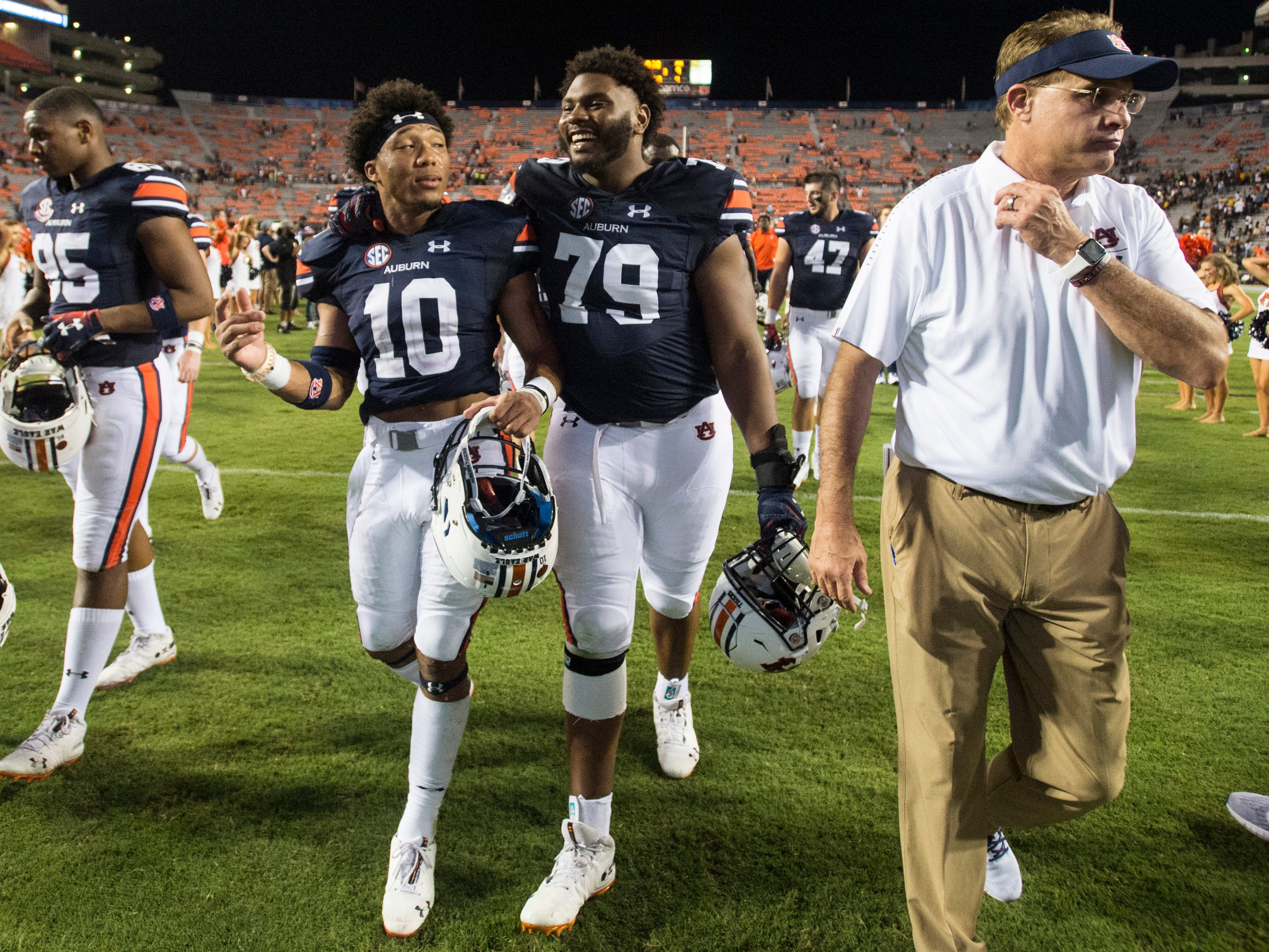 Auburn's Devan Barrett (10) and Andrew Williams (79) walk off the field with head coach Gus Malzahnat Jordan-Hare Stadium in Auburn, Ala., on Saturday, Sept. 8, 2018. Auburn defeated Alabama State 63-9.