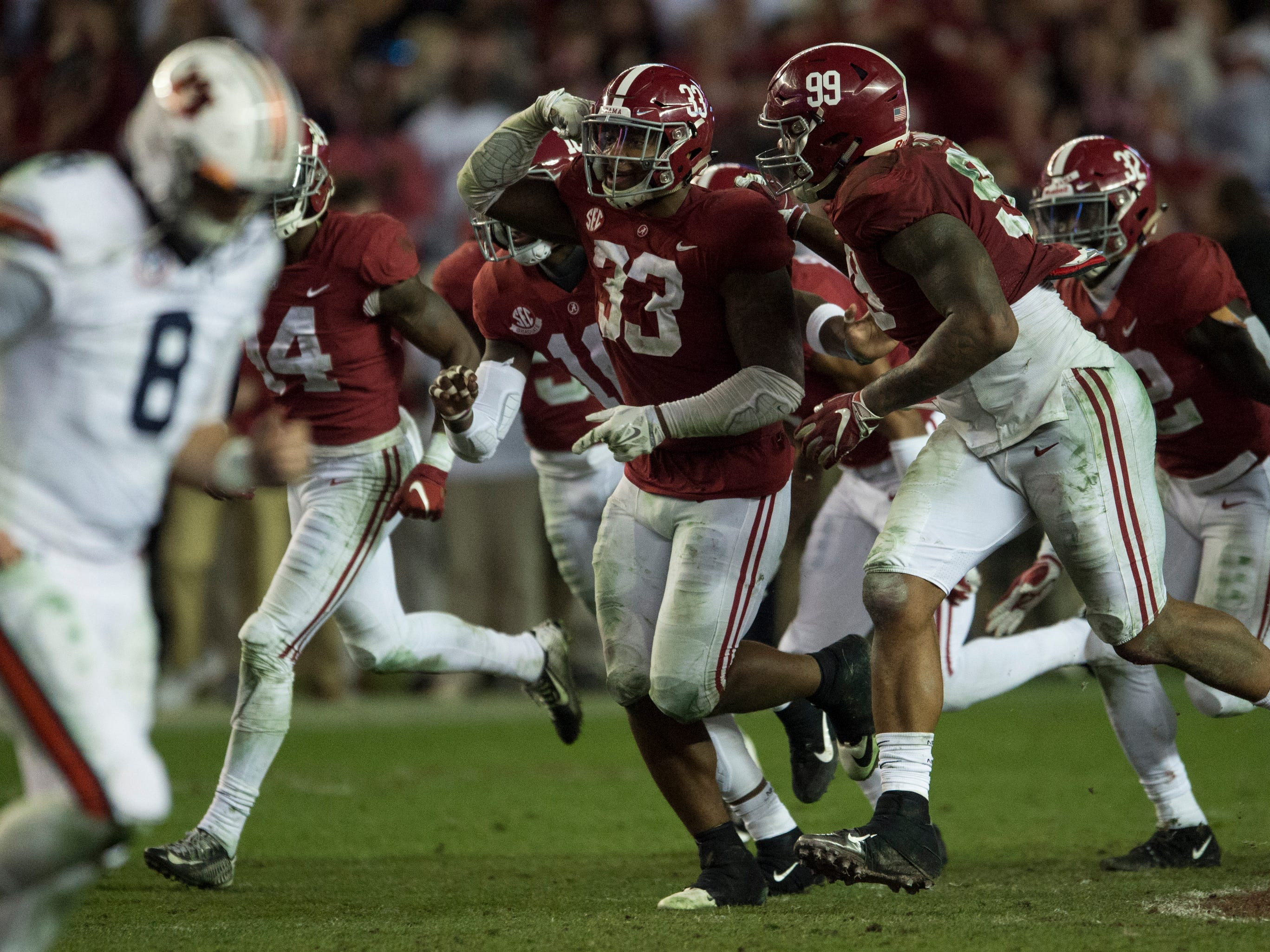 Alabama linebacker Anfernee Jennings (33) celebrates after intercepting the ball as Auburn quarterback Jarrett Stidham (8) runs off the field during the Iron Bowl at Bryant-Denny Stadium in Tuscaloosa, Ala., on Saturday, Nov. 24, 2018. Alabama defeated Auburn 52-21.