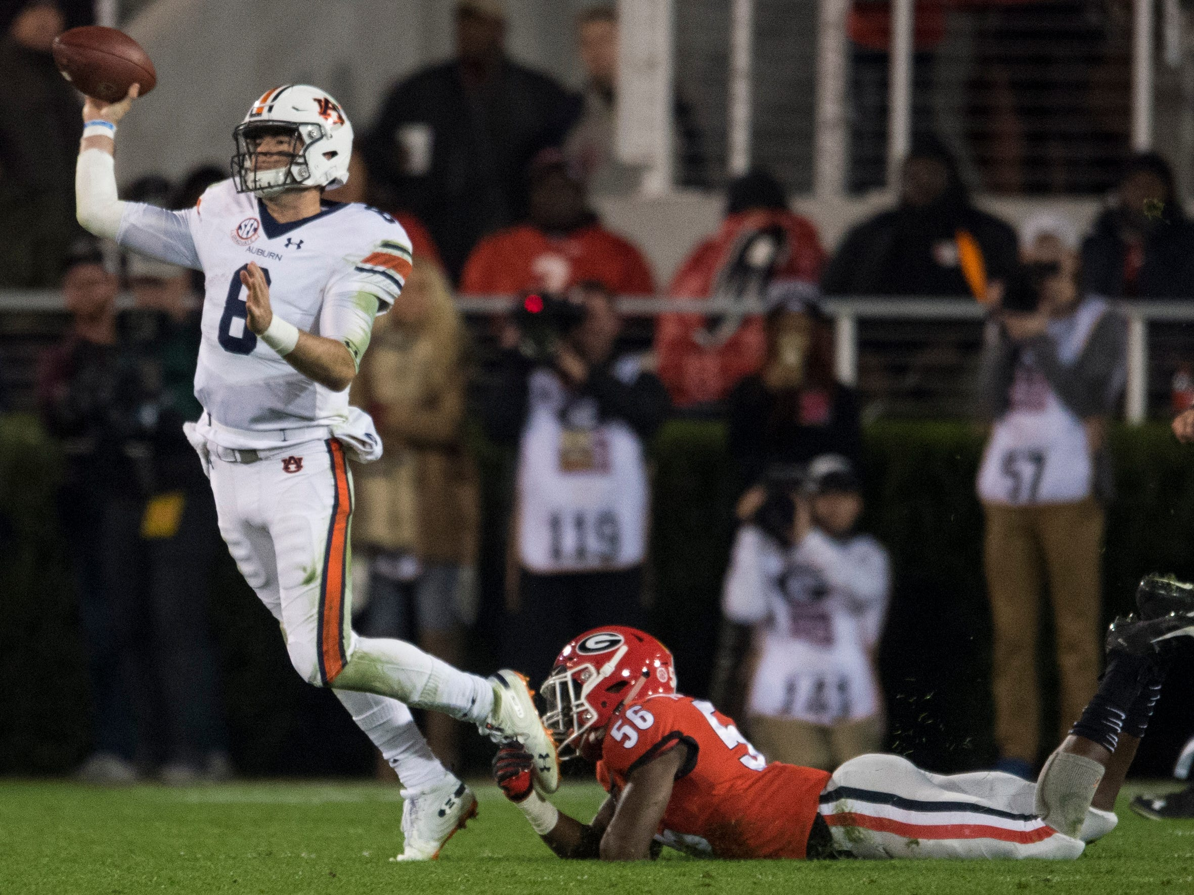 Auburn quarterback Jarrett Stidham (8) is tripped up by Georgia linebacker Adam Anderson (56) as he throws the ball at Sanford Stadium in Athens, Ga., on Saturday, Nov. 10, 2018. Georgia defeated Auburn 27-10.
