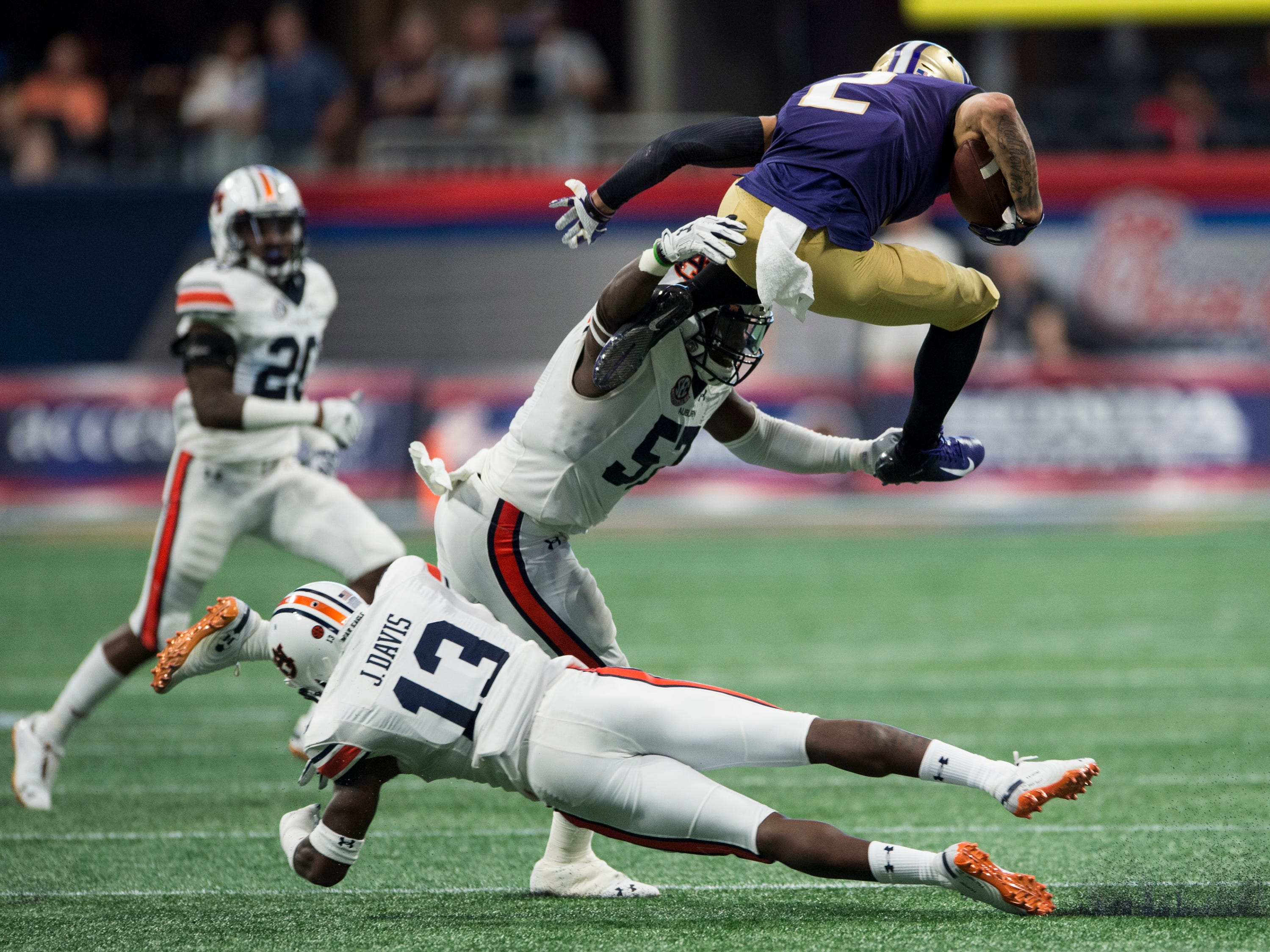Washington's Aaron Fuller (2) keeps over Auburn's Javaris Davis (13) and is tackled in the air by Auburn's Deshaun Davis (57) at Mercedes-Benz Stadium in Atlanta, Ga., on Saturday, Sept. 1, 2018. Auburn leads Washington 15-13 at halftime.