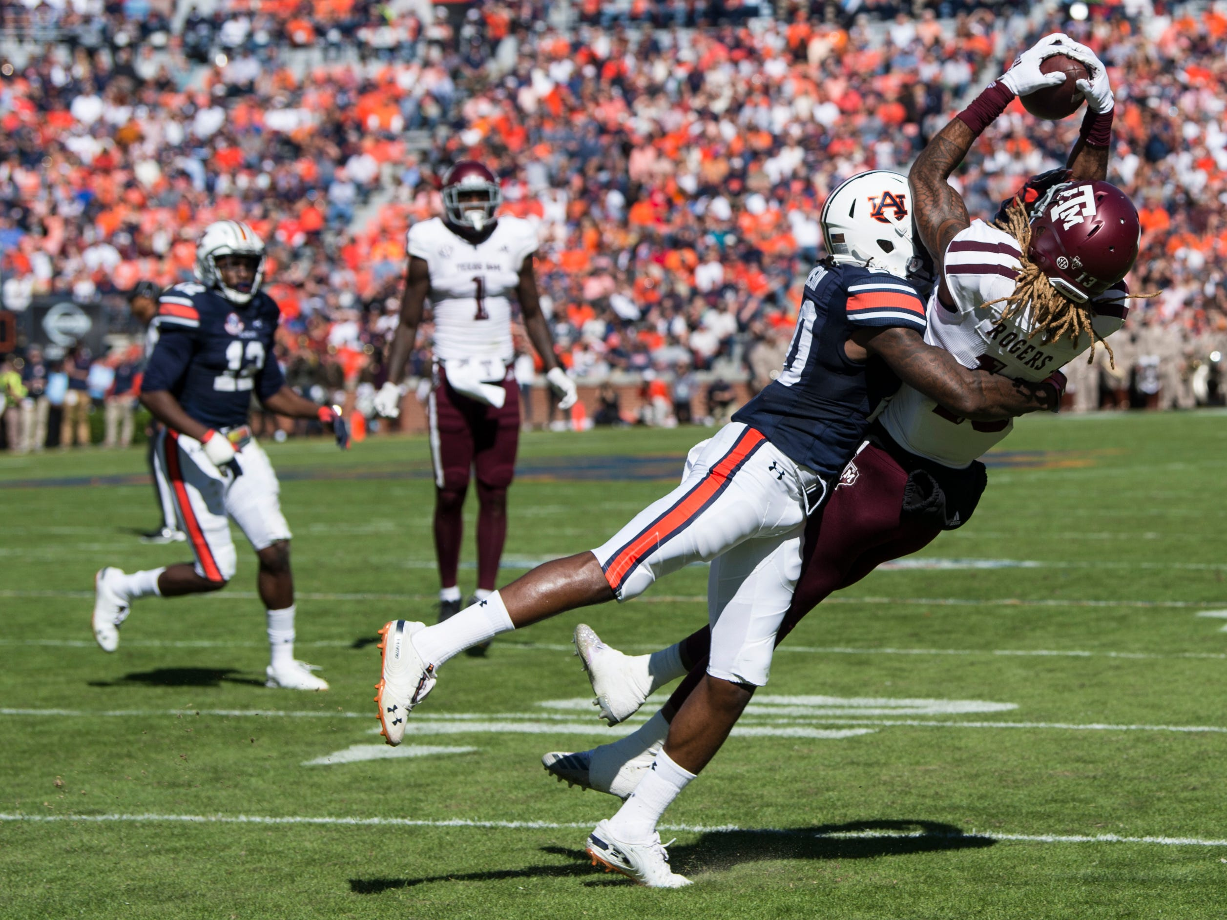 Texas A&M wide receiver Kendrick Rogers (13) pulls in a pass that is eventually dropped as he is hit by Auburn defensive back Jeremiah Dinson (20) at Jordan-Hare Stadium on Saturday, Nov. 3, 2018. Texas A&M leads Auburn17-14 at halftime.