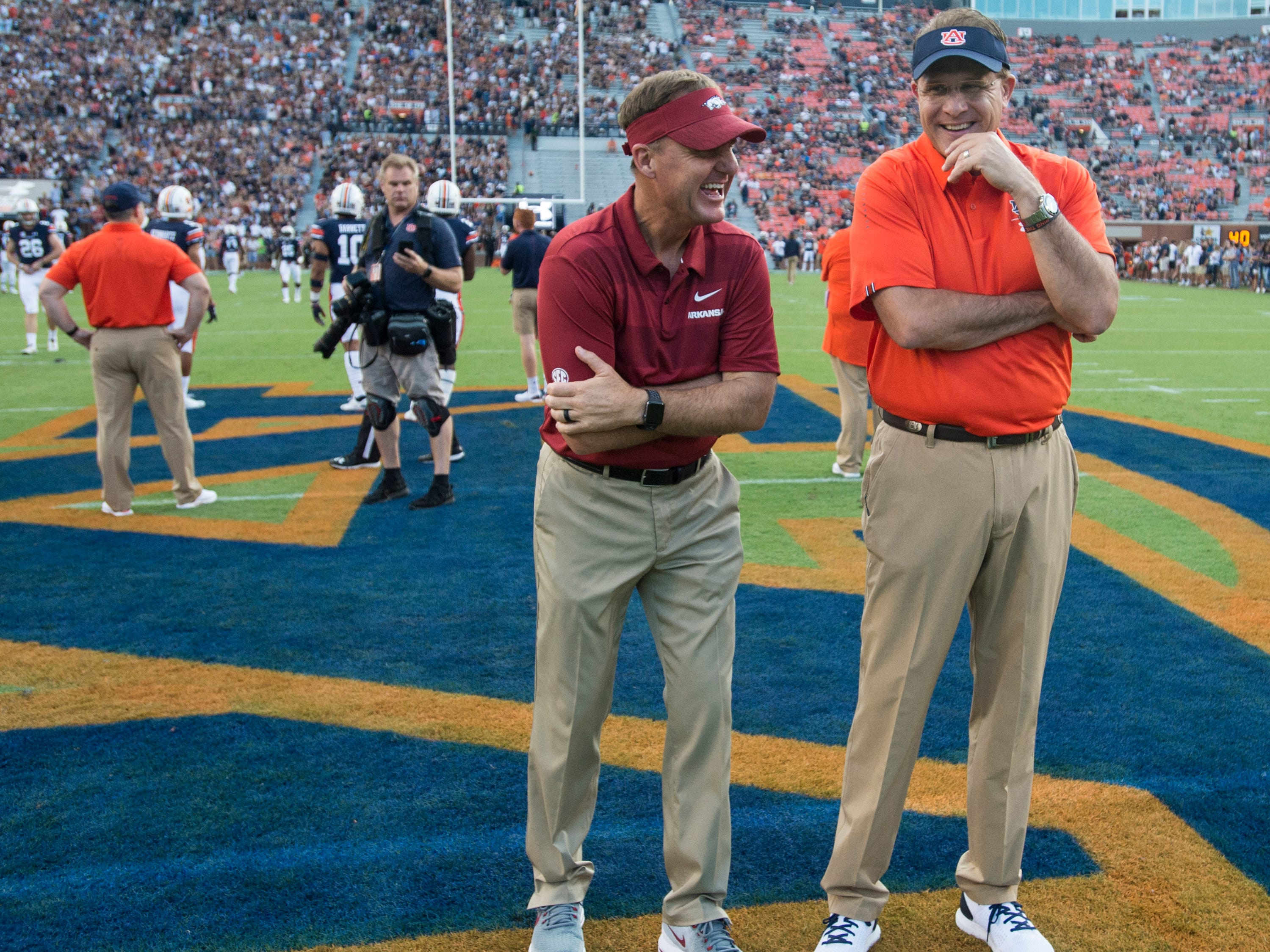 Arkansas head coach Chad Morris and Auburn head coach Gus Malzahn joke on the field as their teams warm up at Jordan-Hare Stadium in Auburn, Ala., on Saturday, Sept. 21, 2018.