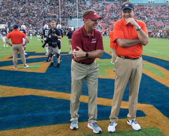 Arkansas head coach Chad Morris and Auburn head coach Gus Malzahn joke on the field as their teams warm up at Jordan-Hare Stadium in Auburn, Ala., on Saturday, Sept. 21, 2018.