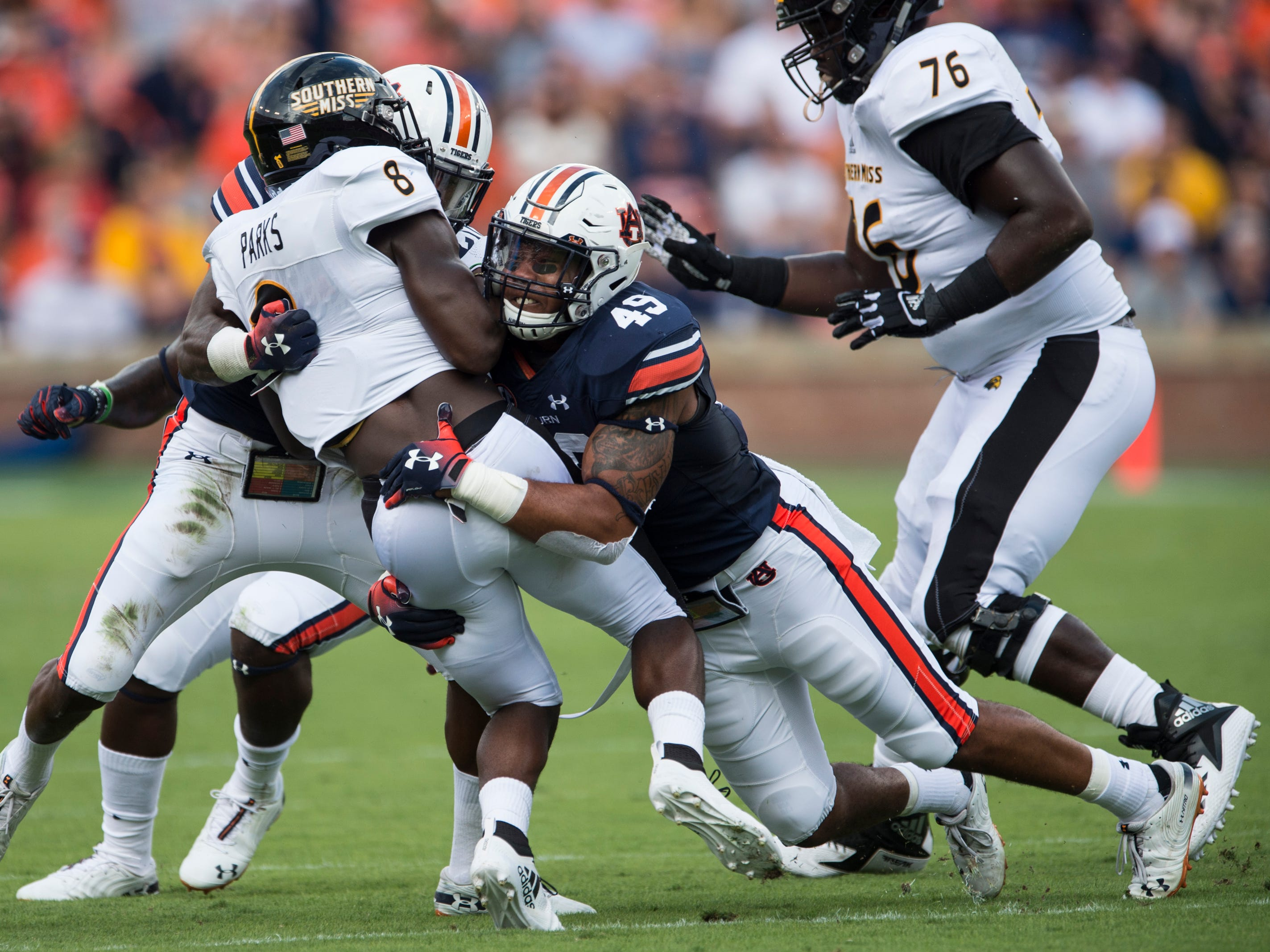 Southern Miss' Tez Parks (8) is taken down by Auburn's Darrell Williams (49) at Jordan-Hare Stadium in Auburn, Ala., on Saturday, Sept. 29, 2018. Auburn leads Southern Miss 14-3, the game went into a weather delay with 4:27 left in the second quarter.