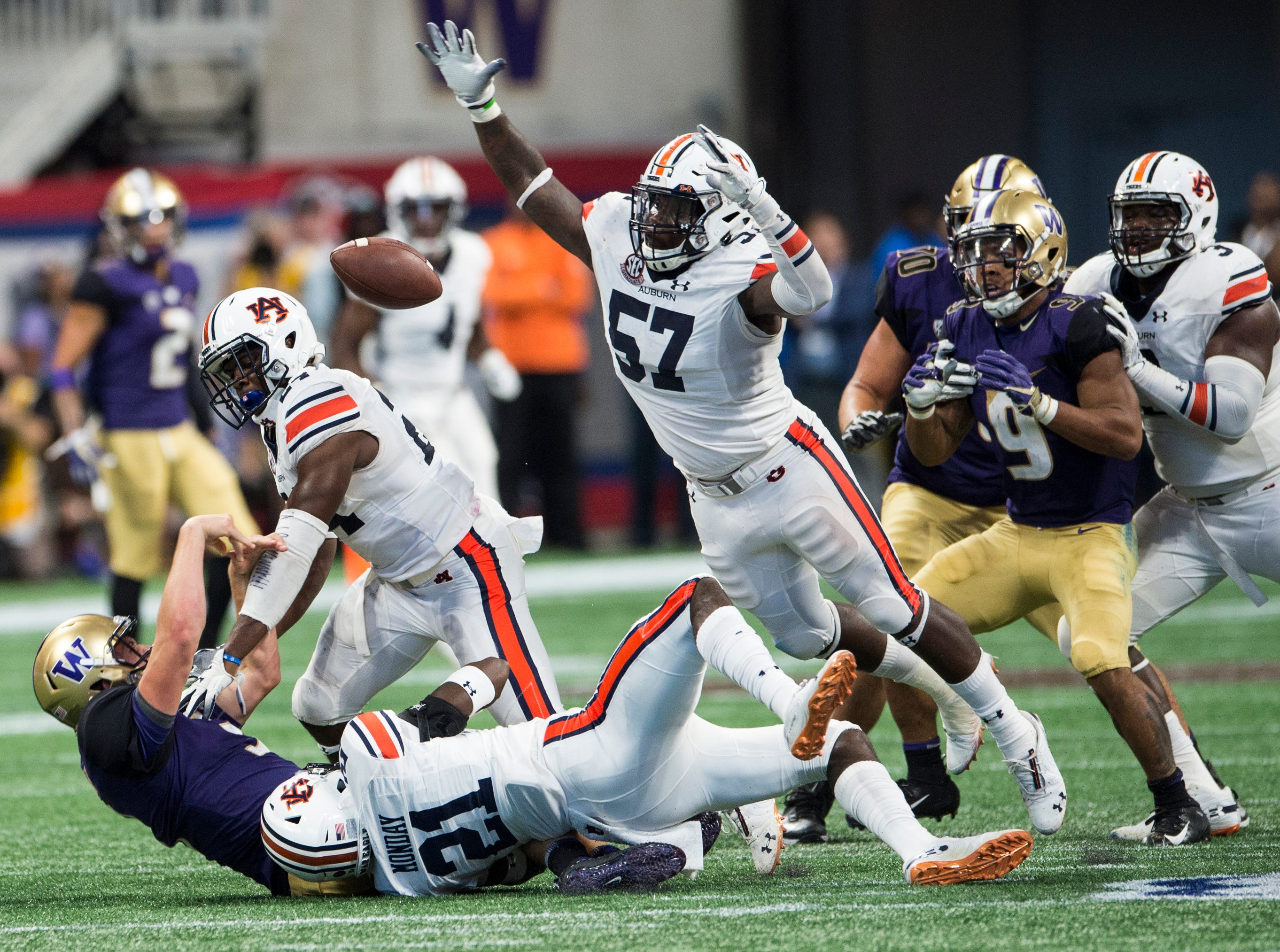 A swarm of Auburn defenders bring down Washington's Jake Browning (3) as he throws a desperation pass on fourth down at Mercedes-Benz Stadium in Atlanta, Ga., on Saturday, Sept. 1, 2018. Auburn defeated Washington 21-16 in the Chick-fil-a Kickoff Game.