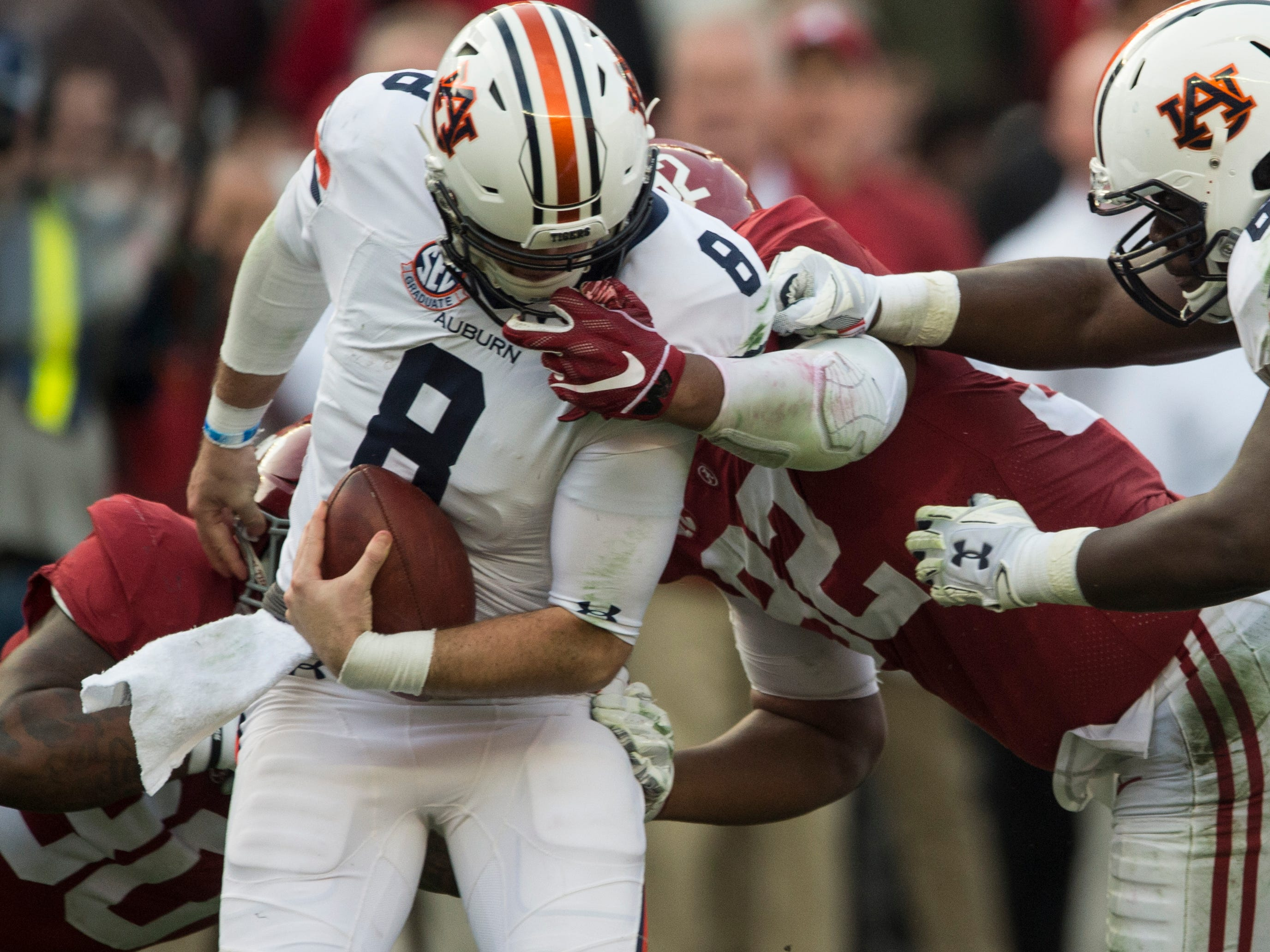 Auburn quarterback Jarrett Stidham (8) is sacked by Alabama defensive lineman Quinnen Williams (92) during the Iron Bowl at Bryant-Denny Stadium in Tuscaloosa, Ala., on Saturday, Nov. 24, 2018. Alabama leads Auburn 17-14 at halftime. A face mask penalty against Alabama was called on the play.