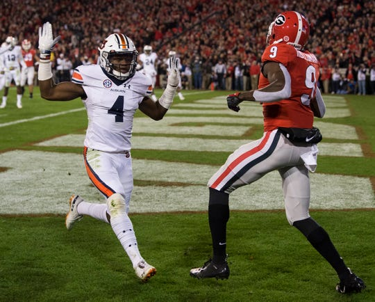 Auburn defensive back Noah Igbinoghene (4) puts his hands up after deflecting a pass in the end zone intended for Georgia wide receiver Jeremiah Holloman (9) at Sanford Stadium in Athens, Ga., on Saturday, Nov. 10, 2018. Georgia leads Auburn 20-10 at halftime.