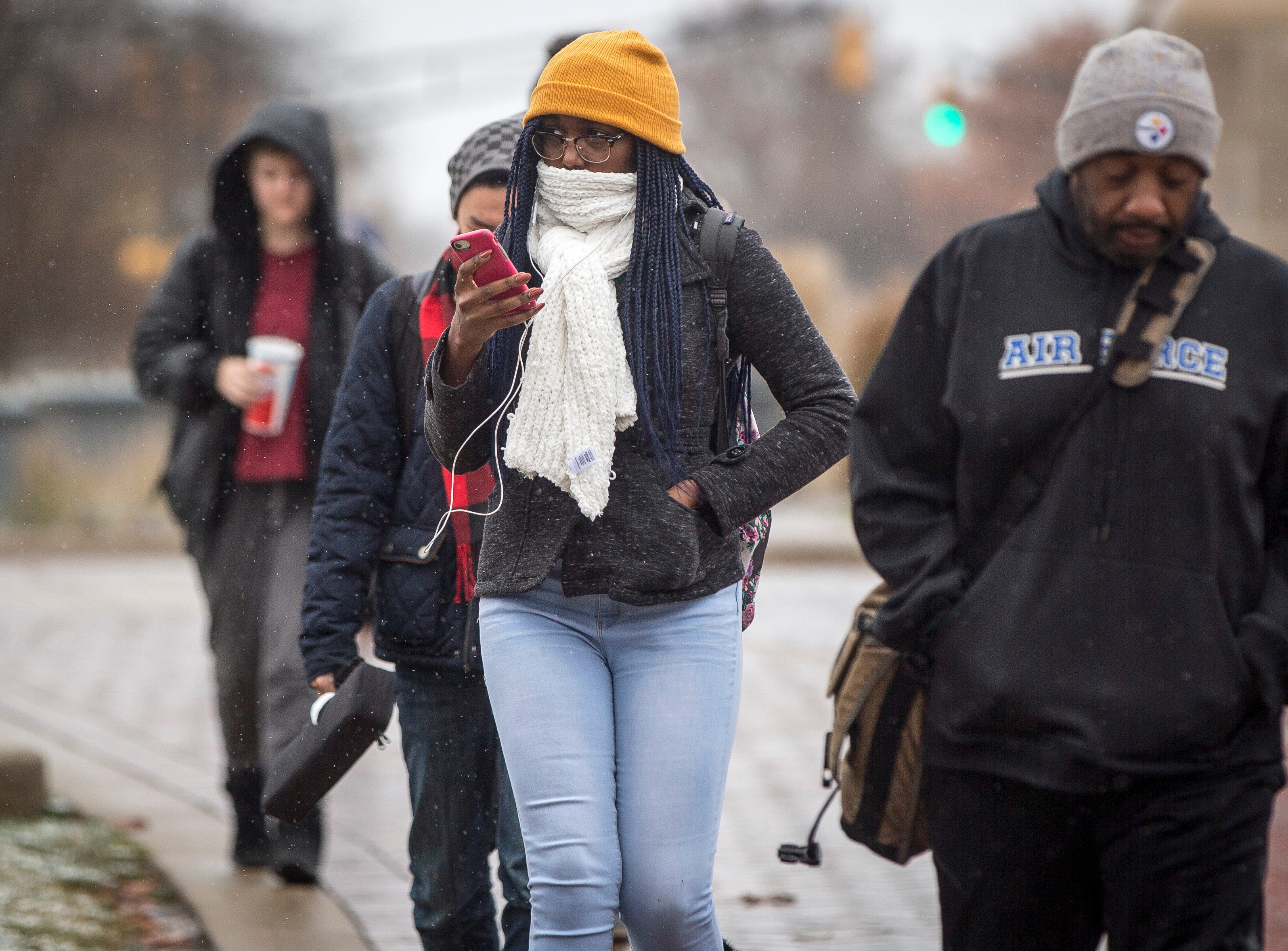 Ball State University students wander through the winter mix that fell through most of the afternoon on Monday. The National Weather service isn't predicting more snow, but temperatures will remain near or below freezing.