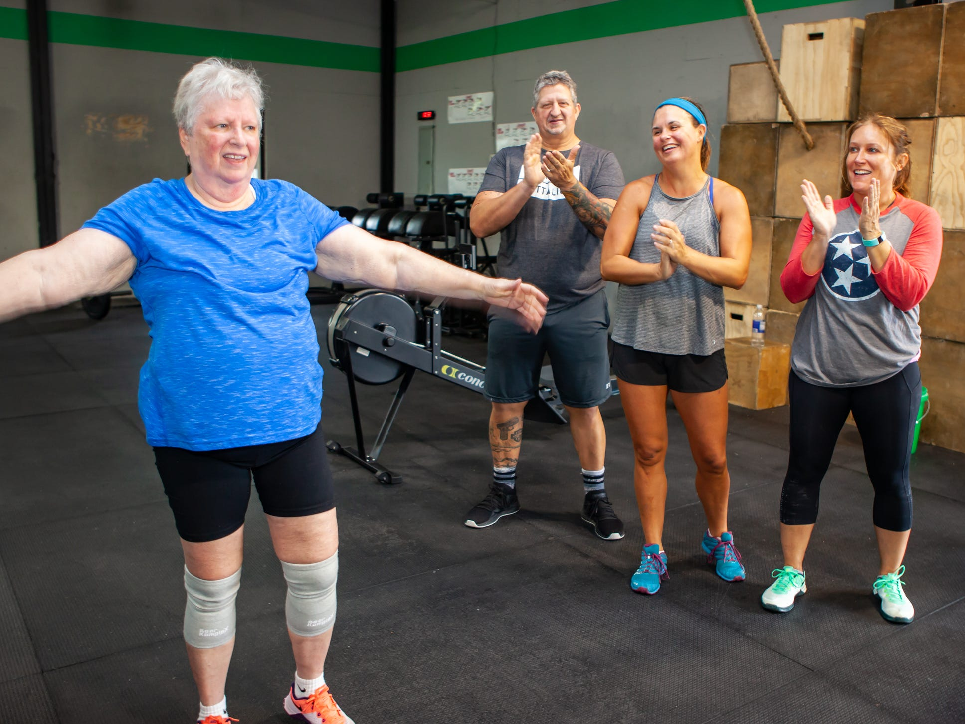 Lynda Miles gets a round of applause after finishing a workout at the CrossFit Barbell Batallion in downtown Murfreesboro.