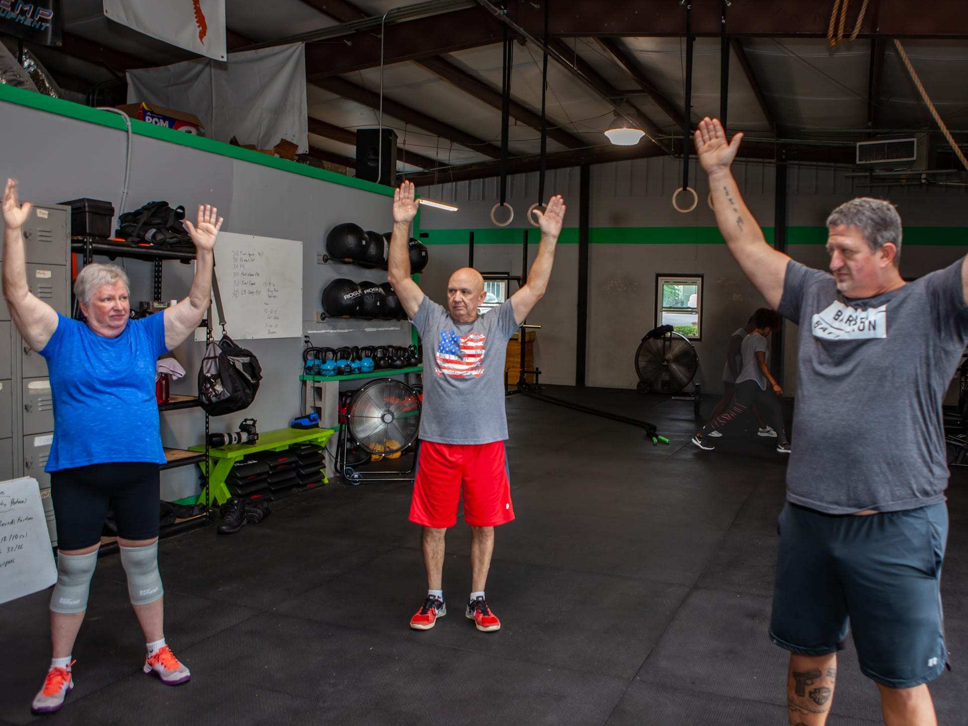 Lynda, Alton and Tim Miles, from left, stretch prior to a workout at CrossFit Barbell Batallion in downtown Murfreesboro. Tim Miles is a trainer and Lynda and Alton are his parents.