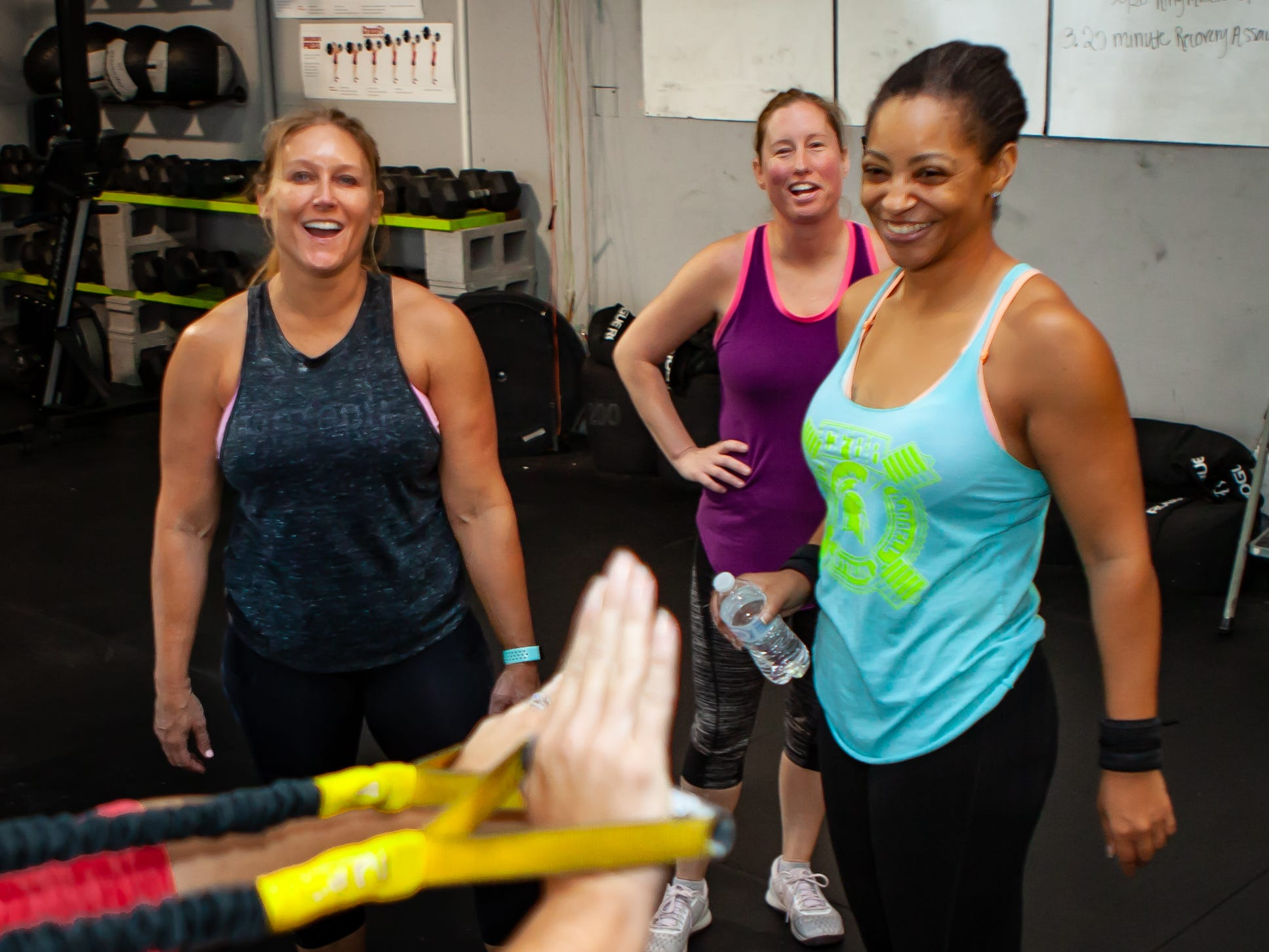 A group of CrossFit athletes at Barbell Batallion in downtown Murfreesboro encourage a member during a workout.