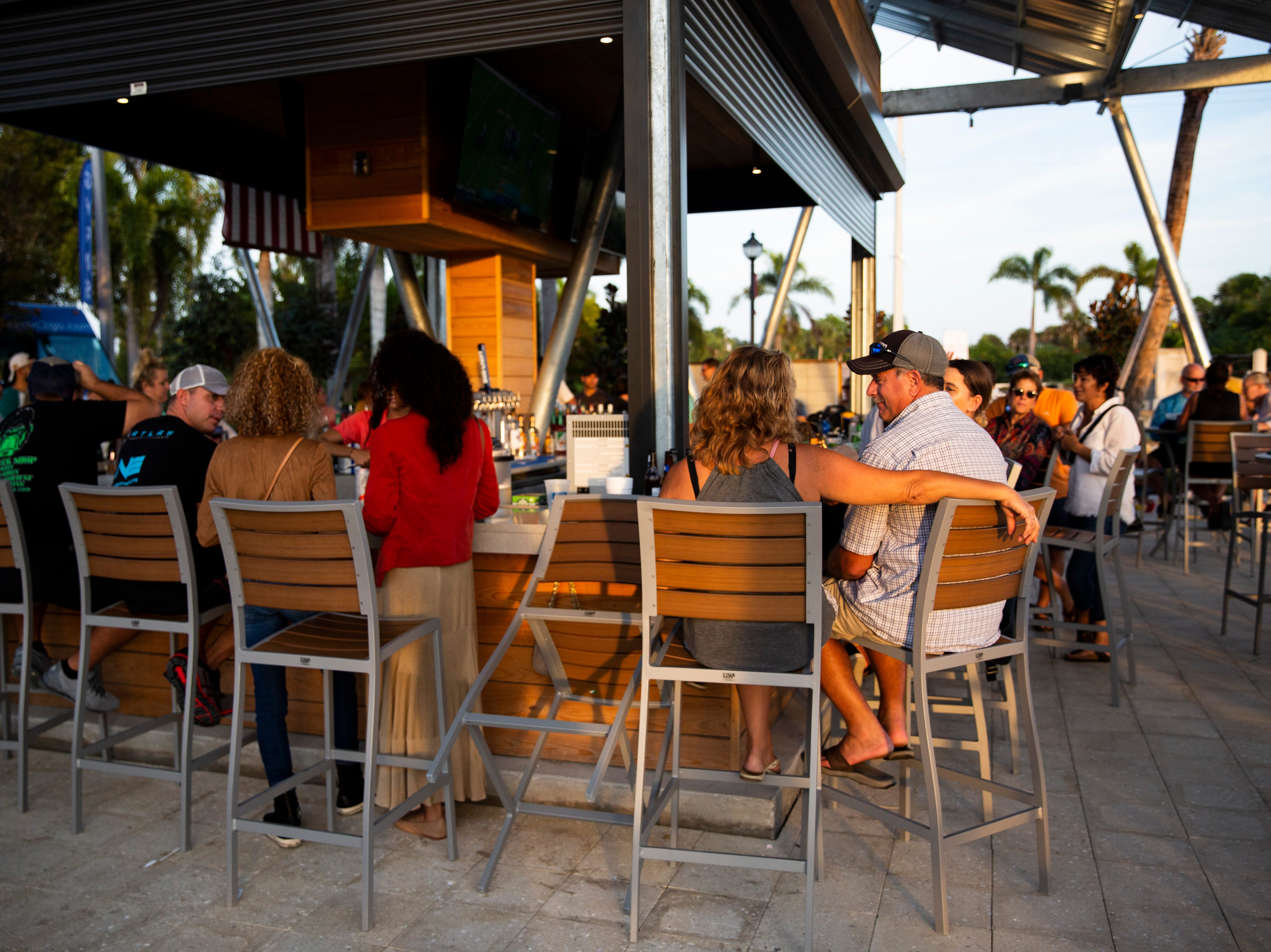 Customers sit around the bar as the sun sets on Sunday, November 25, 2018, at Celebration Park in Naples.