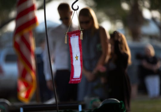 "Justin Evers, his wife, Rebecca Evers, and their daughter Kate Evers stand beside the grave of Justin's grandmother, Carlynn ""Polly"" Crews, at Hodges Funeral Home at Naples Memorial Gardens on Monday, Nov. 26, 2018. Crews, 93, was the oldest Gold Star Mother in Florida."