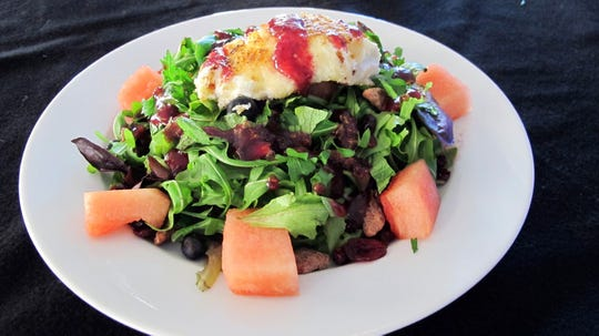 Naples Coastal Kitchen's Watermelon Salad has lightly breaded goat cheese drizzled with a raspberry vinaigrette over mixed greens, blueberries, candied pecans and watermelon cubes.