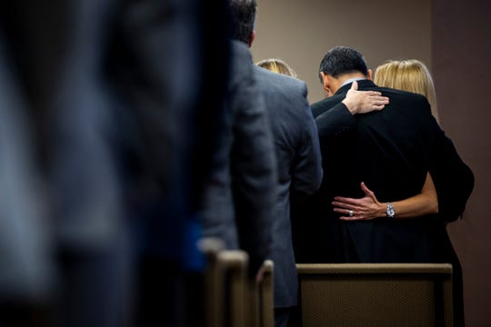 Loved ones hug during the memorial service for Jon MacDonough on Saturday, Nov. 24, 2018, at Golden Gate Kingdom Hall of Jehovah's Witnesses in Golden Gate.
