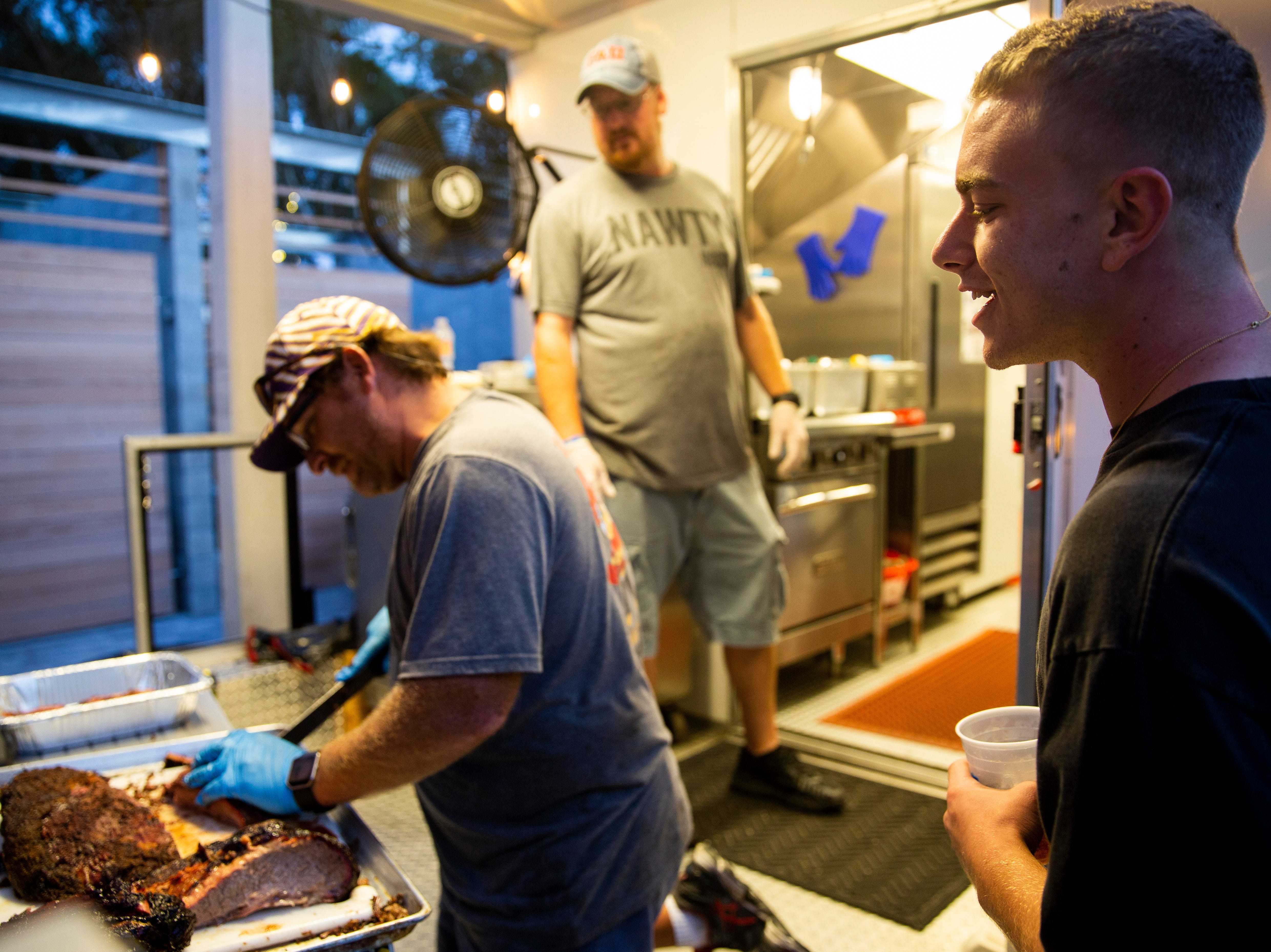 David Mazzarella, right, watches as Aric Tousignant slices a brisket at the Nawty Hogg BBQ food truck on Sunday, November 25, 2018, at Celebration Park in Naples.