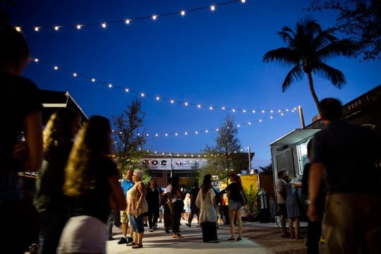 Customers walk down the lane of food trucks on Sunday, Nov. 25, 2018, at Celebration Park in the Bayshore area of East Naples.