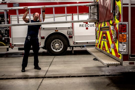 Newark fire Captain, Mike Bolte, slides the ladder back into the firetruck after making sure it was in good working order. Each morning firefighters and EMTs check their equipment and make sure everything is stocked for the day.