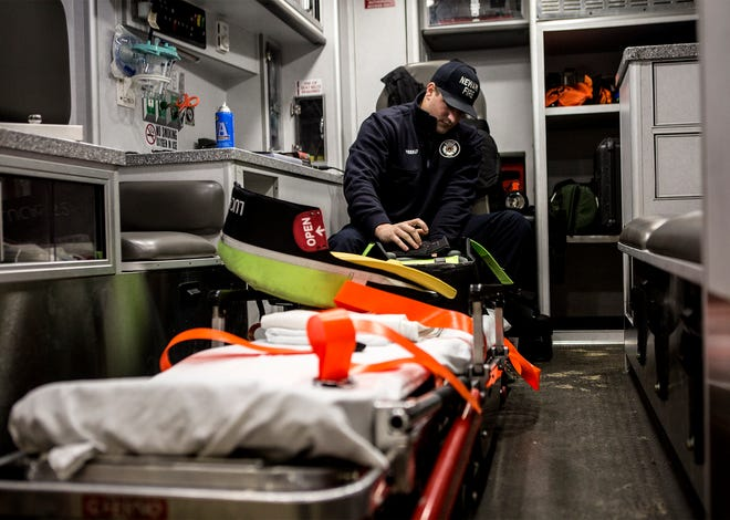 Newark EMT, Kyle Weekly, restocks an ambulance at Newark's Fire station 1. Each morning firefighters and EMTs check their equipment and make sure everything is stocked for the day.
